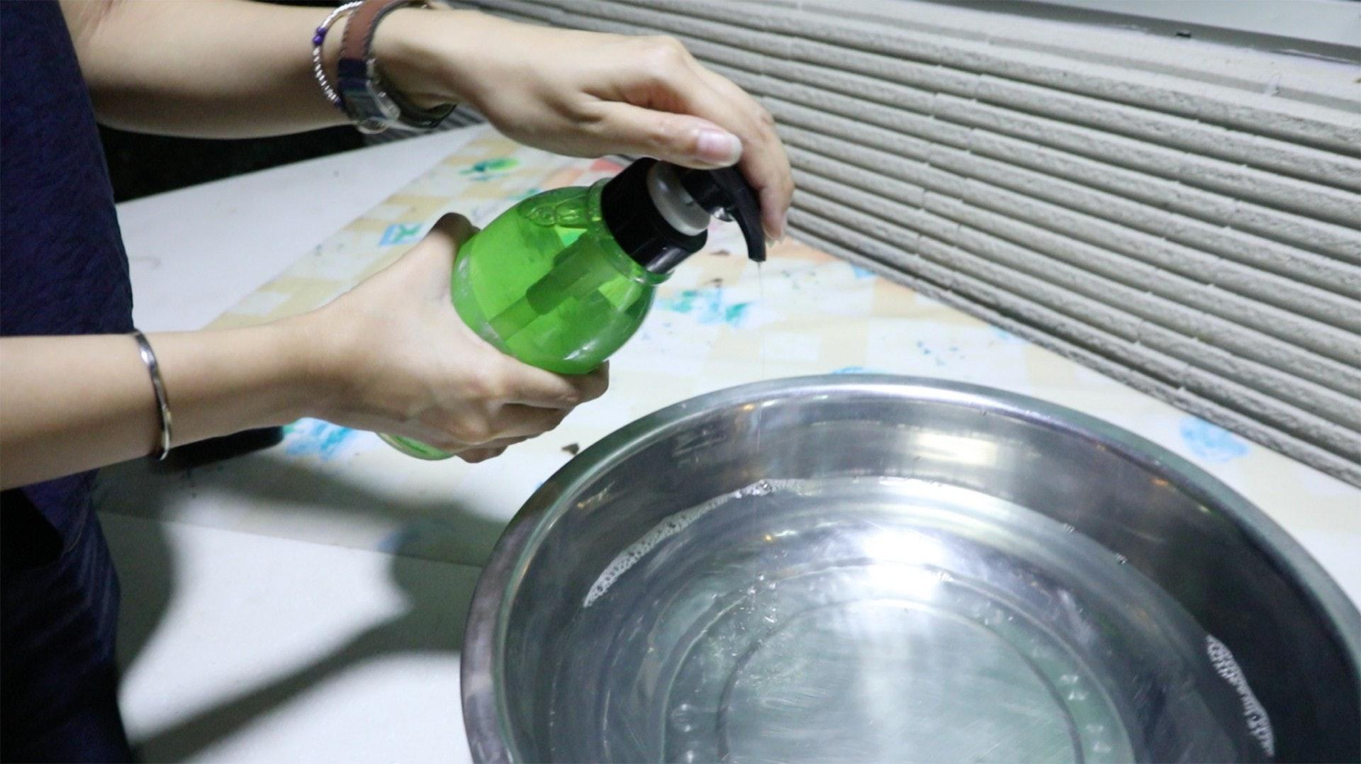 將小量洗潔精加入水盆中。(岑卓熹攝)