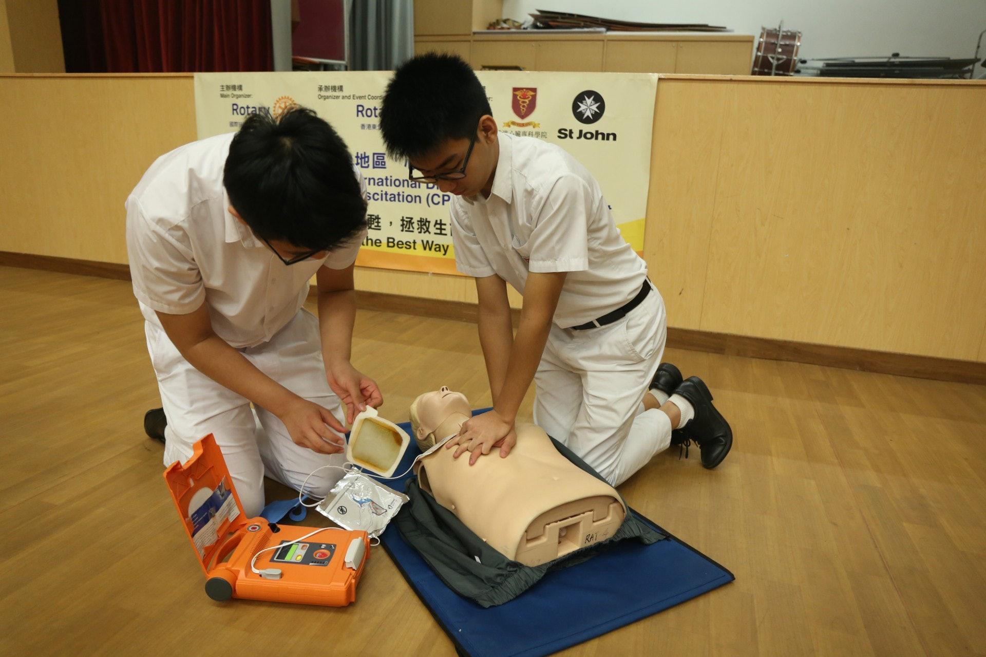 學生以人型公仔示範用AED機進行心肺復甦法急救。(陳百灝攝)
