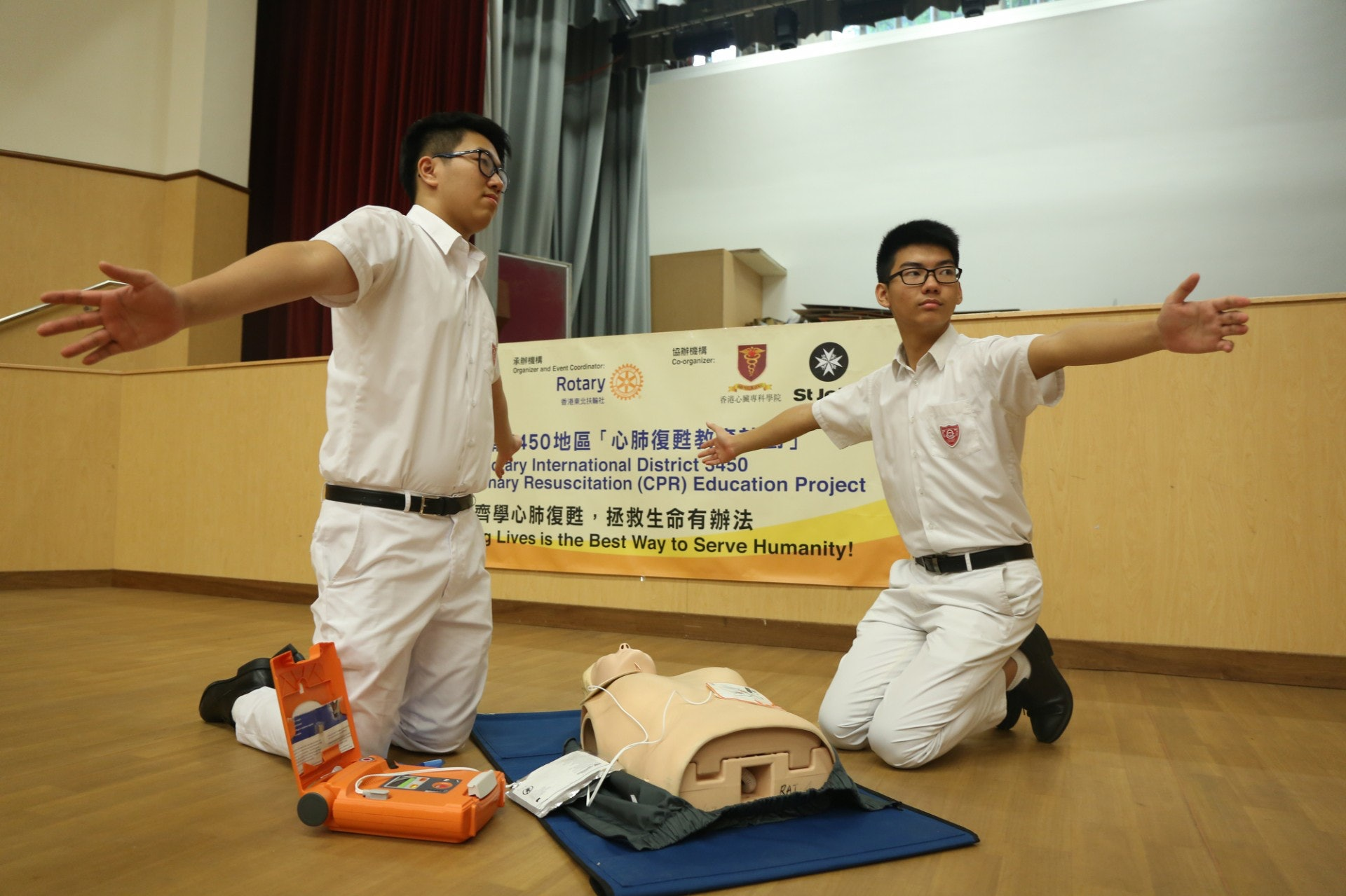 學生示範當用AED機進行電擊前,需張開雙手,以免接觸到電流。(陳百灝攝)