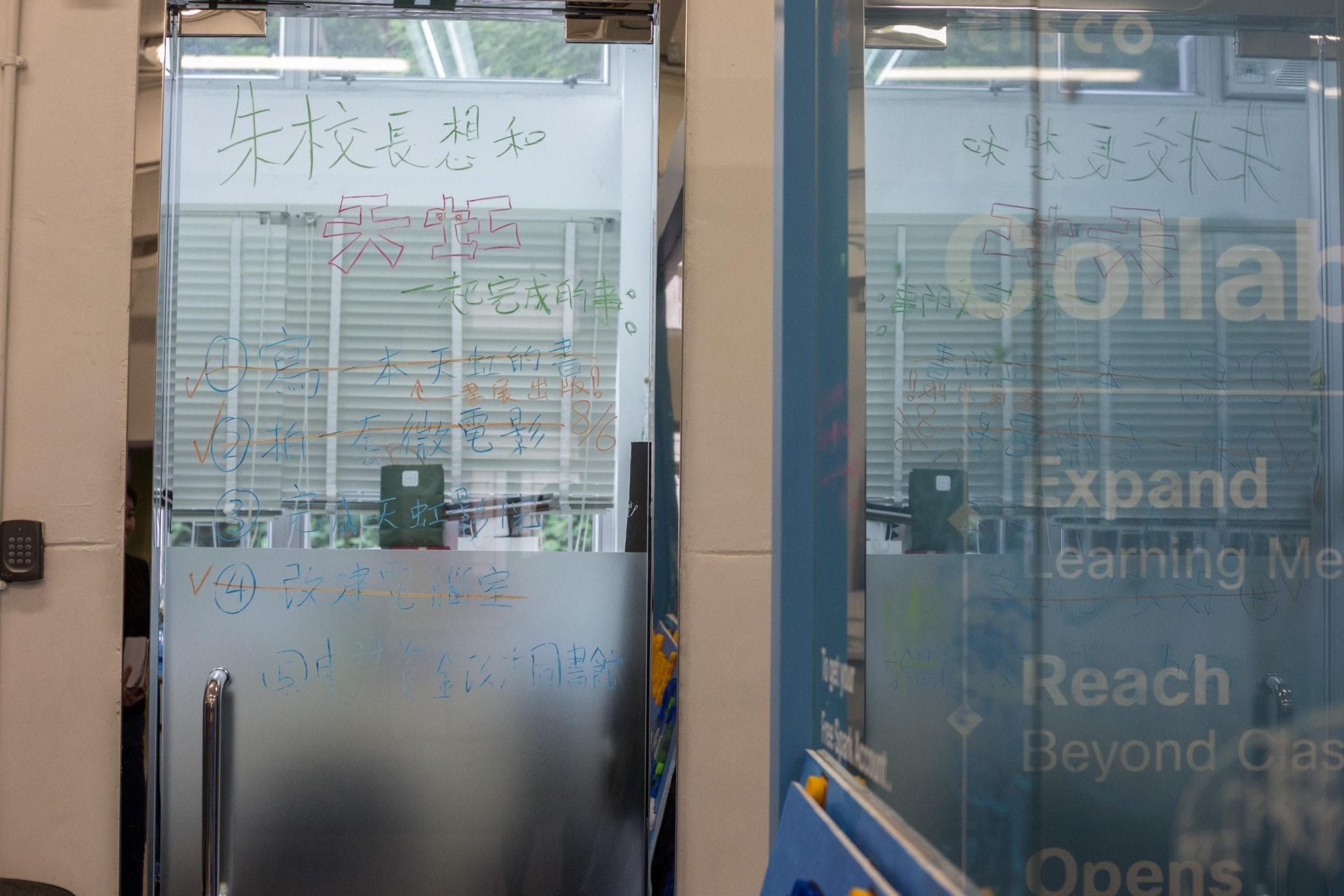 朱子穎在校長室的玻璃門外,寫上自己希望與天虹一同完成的目標。(梁鵬威攝)