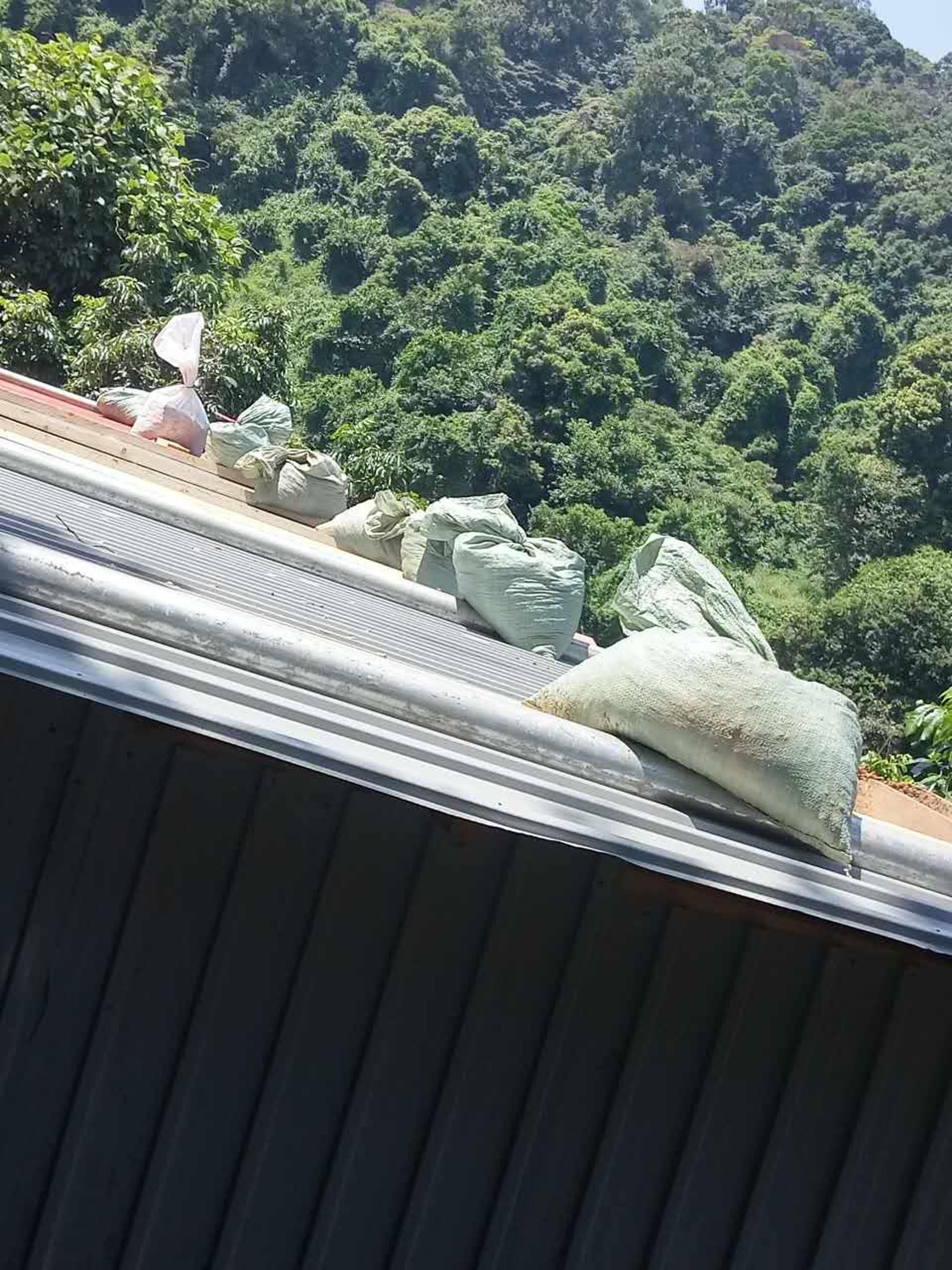 颱風來襲前夕,美虹和萬豪父母在寮屋頂加上沙包,以防被颱風吹塌。