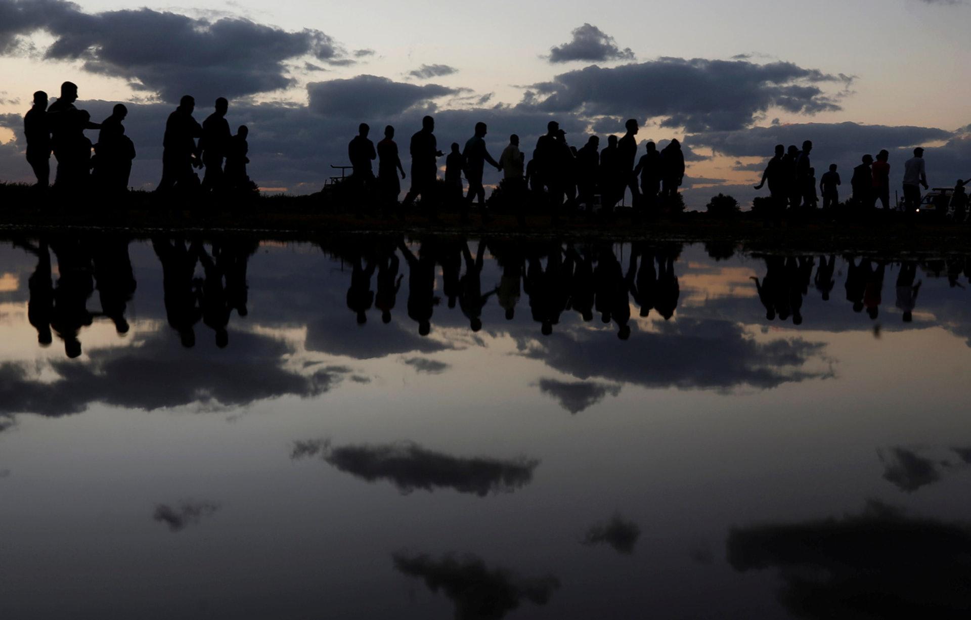 10月26日,雨後,地上積水反映出巴勒斯坦示威者的身影。(Mohammed Salem/路透社)