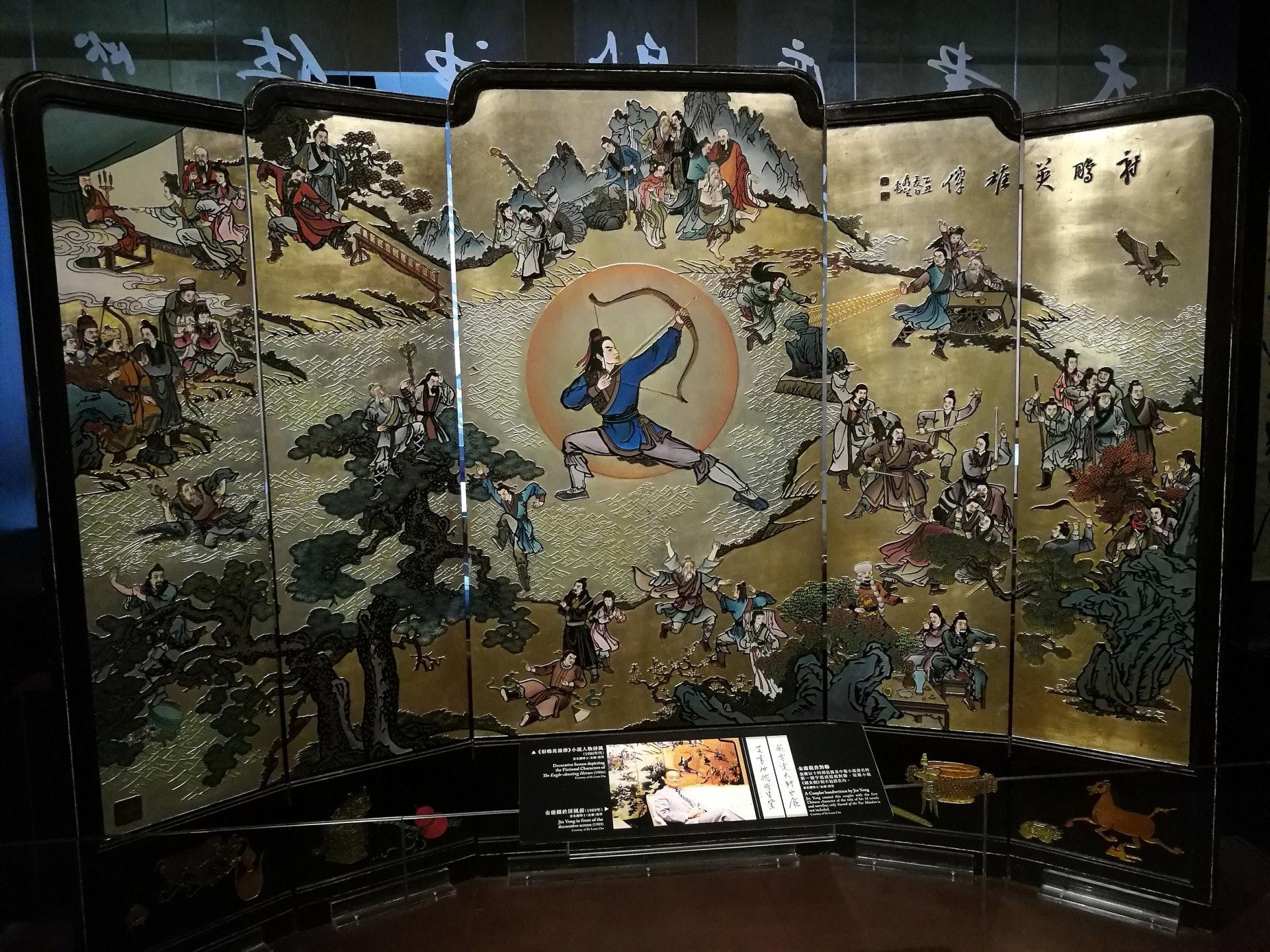 繪畫金庸小說人物的屏風,金庸曾在屏風前拍照留影。(VCG)