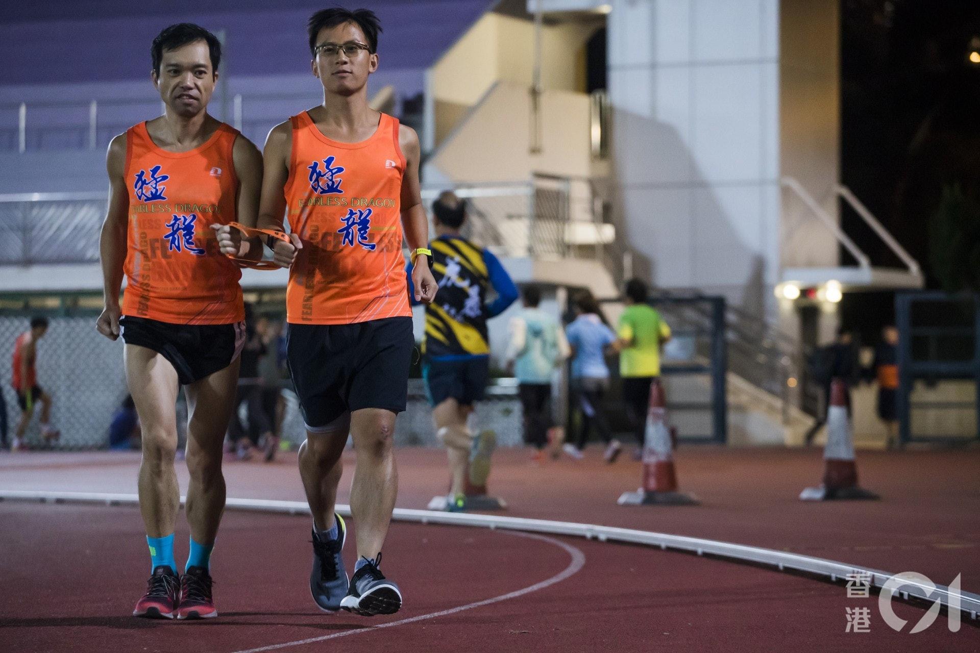 身穿橙衣的浩良(左)與Donald(右),無懼當天冷鋒吹襲,在運動場並肩而行。(余俊亮攝)