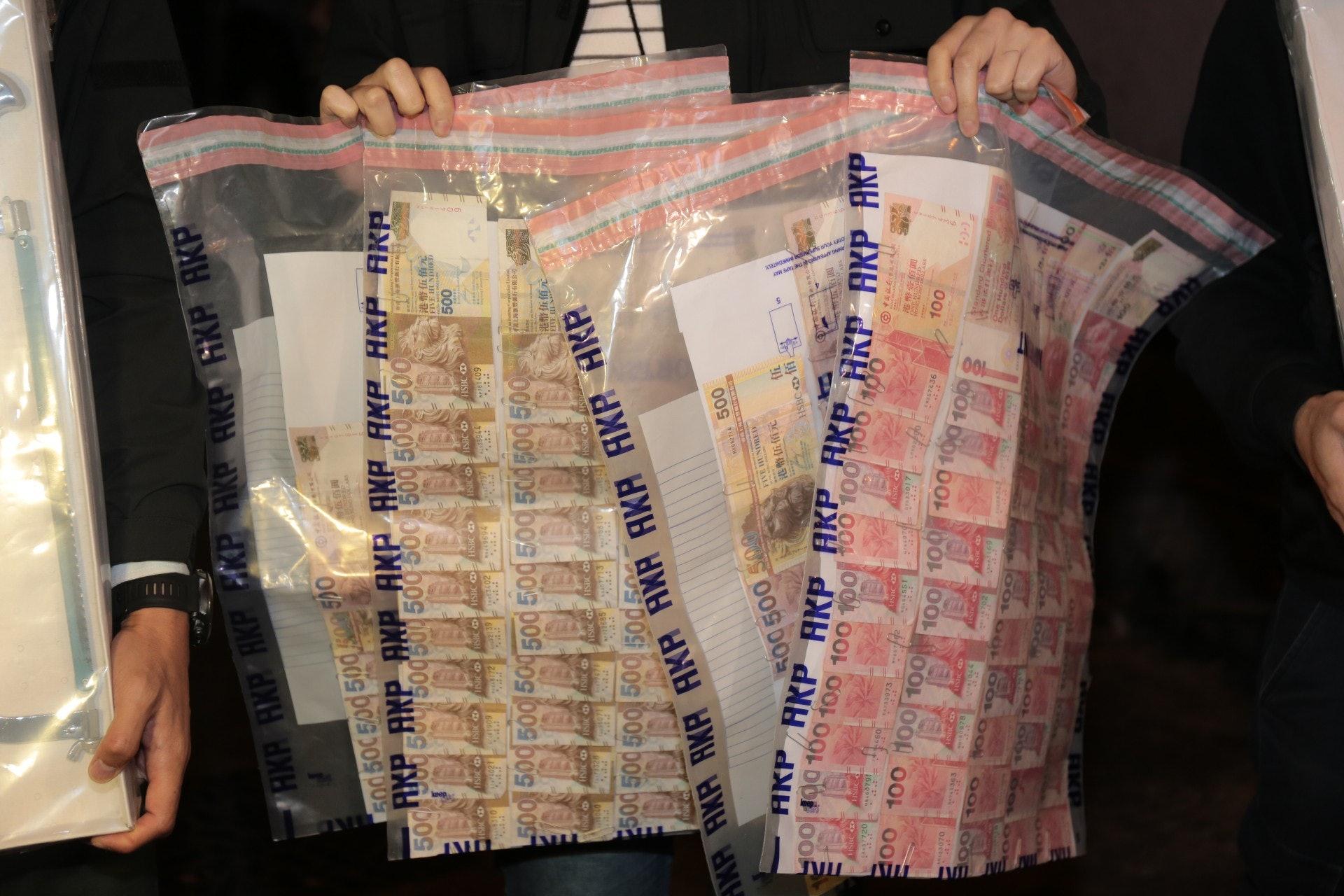 警方在一名男子的背囊中起回夾萬內的現金。(余睿菁攝)