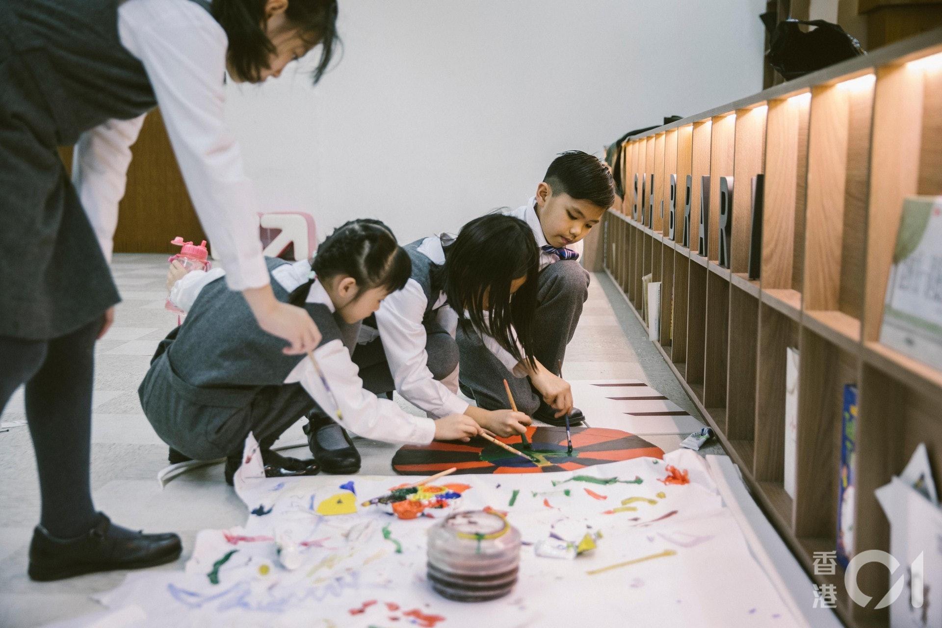 放學以後,學生們用顏料在紙皮上塗出圖案,畫出花車的車輪。(鄭子峰攝)