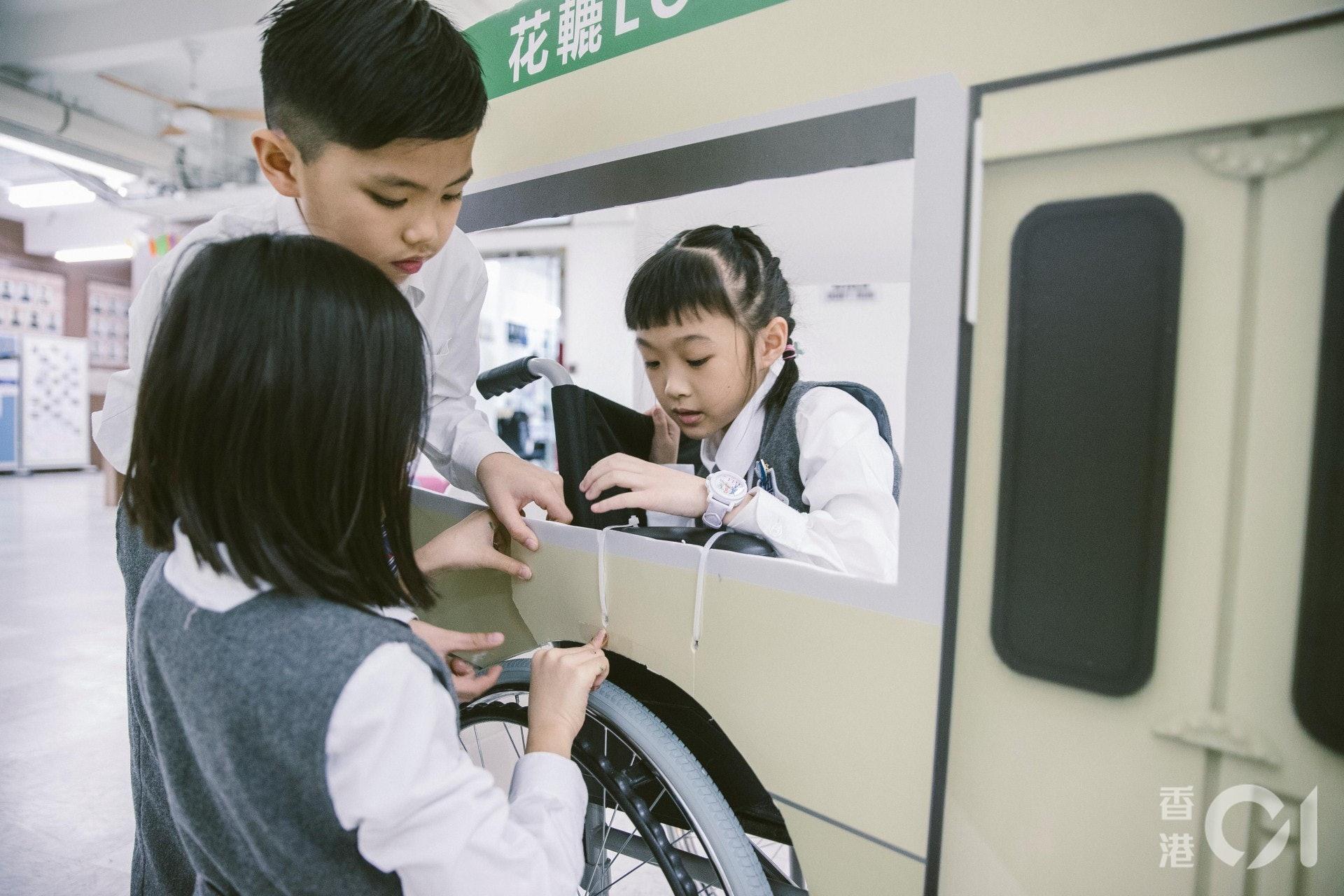 德萃小學的學生幫忙改造輪椅,將之變成一輛「十六座小巴」花車。(鄭子峰攝)
