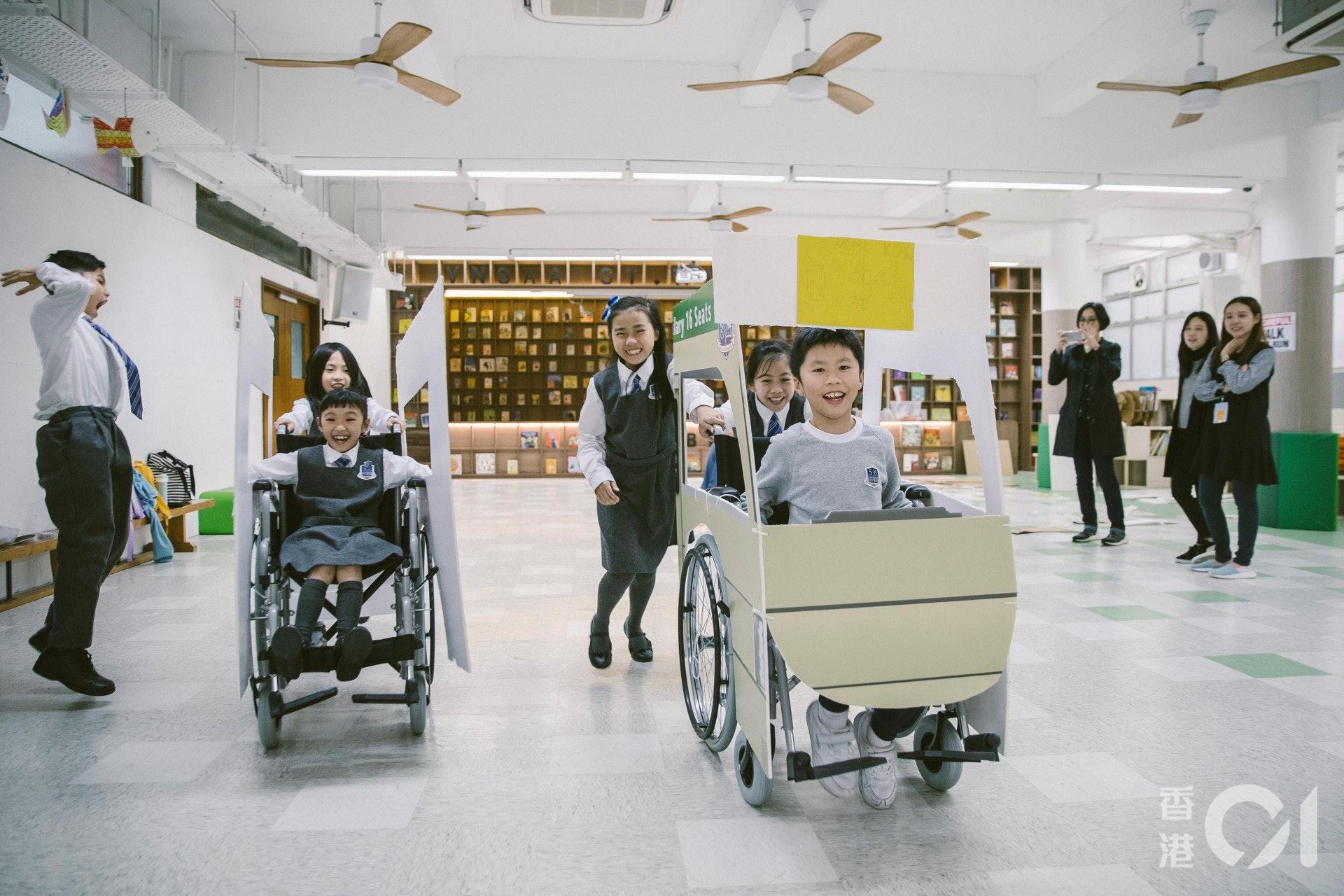 推着同學在禮堂中奔馳,輪椅在學生們的手中變成了一件玩具。(鄭子峰攝)