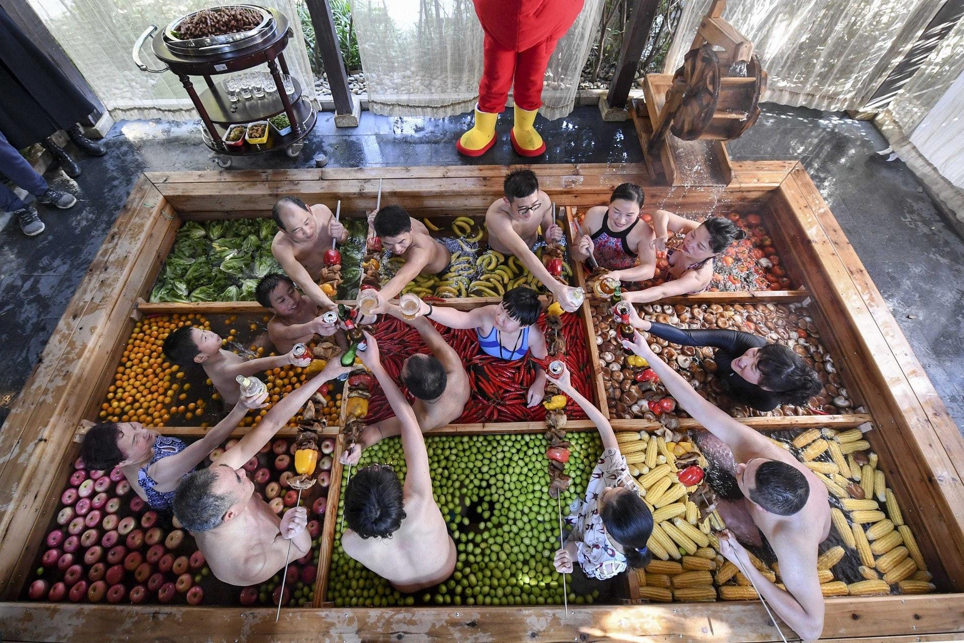 為迎接豬年,有杭州酒店推出九宮格火鍋溫泉,讓顧客泡浸各種火鍋配料時同時享用巨型豬肉串。(視覺中國)