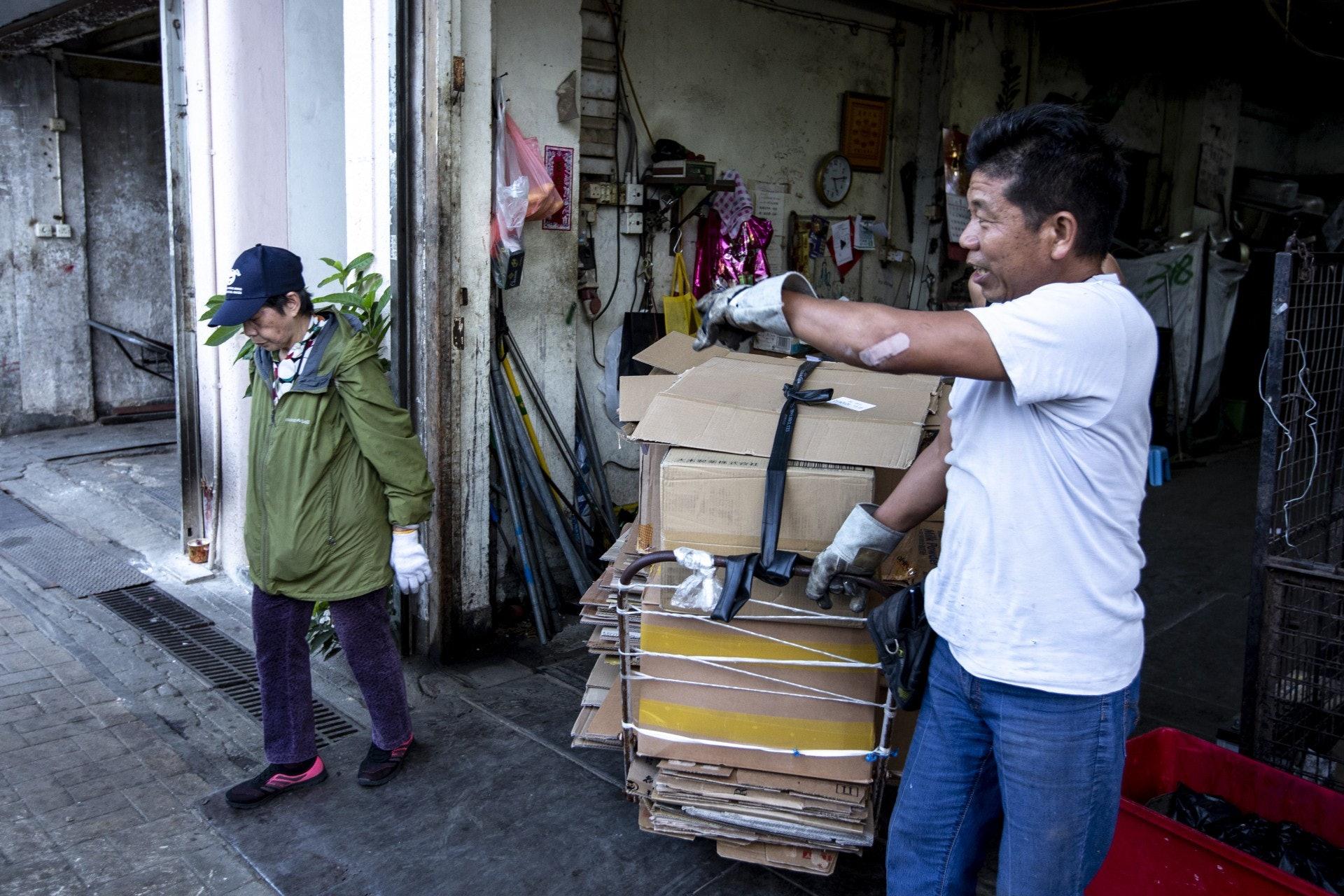見到回收商後,量度重量、交出紙皮、收到金錢,一切在短於一分鐘的時間內完成。(羅君豪攝)