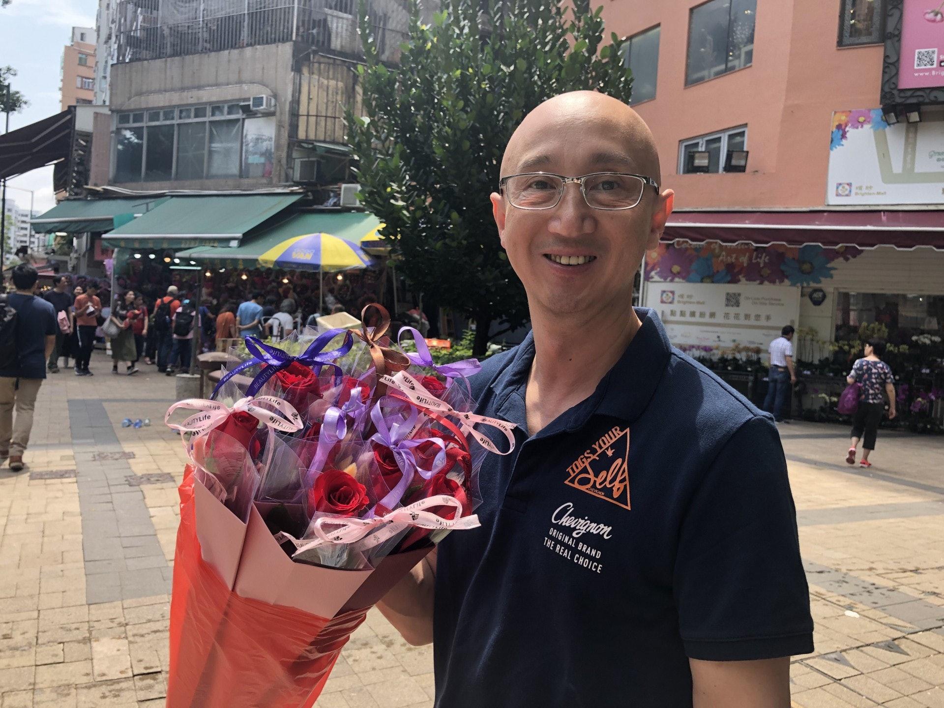 李先生一口氣買了九枝獨立包裝玫瑰花,與家人分享快樂。(勞敏儀攝)