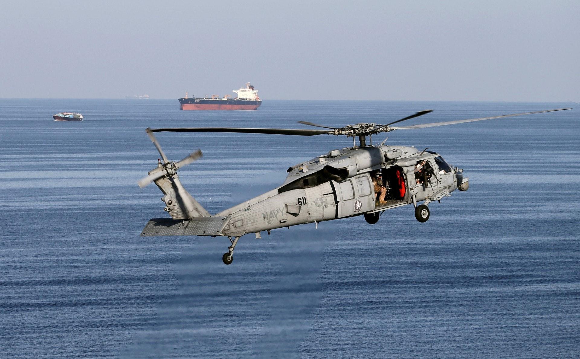 一架美國海軍直升機飛近霍爾木茲海峽,遠方可見一艘運油輪。(路透社)