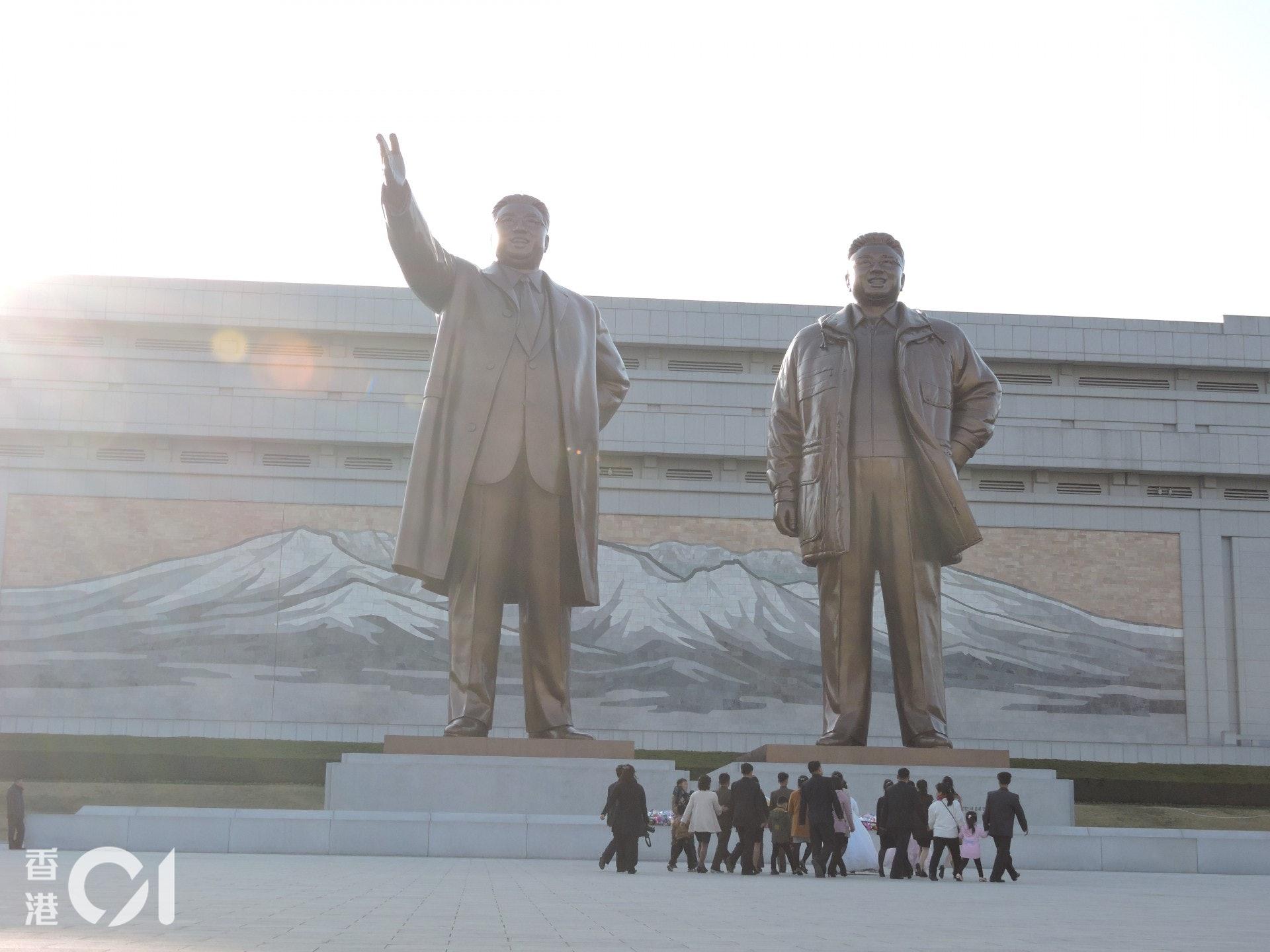 在萬壽台紀念碑兩位領導人金日成和金正日的銅像前,快將結為夫婦的新人及親友上前獻花,希望得到二人的祝福。(歐陽翠詩攝)