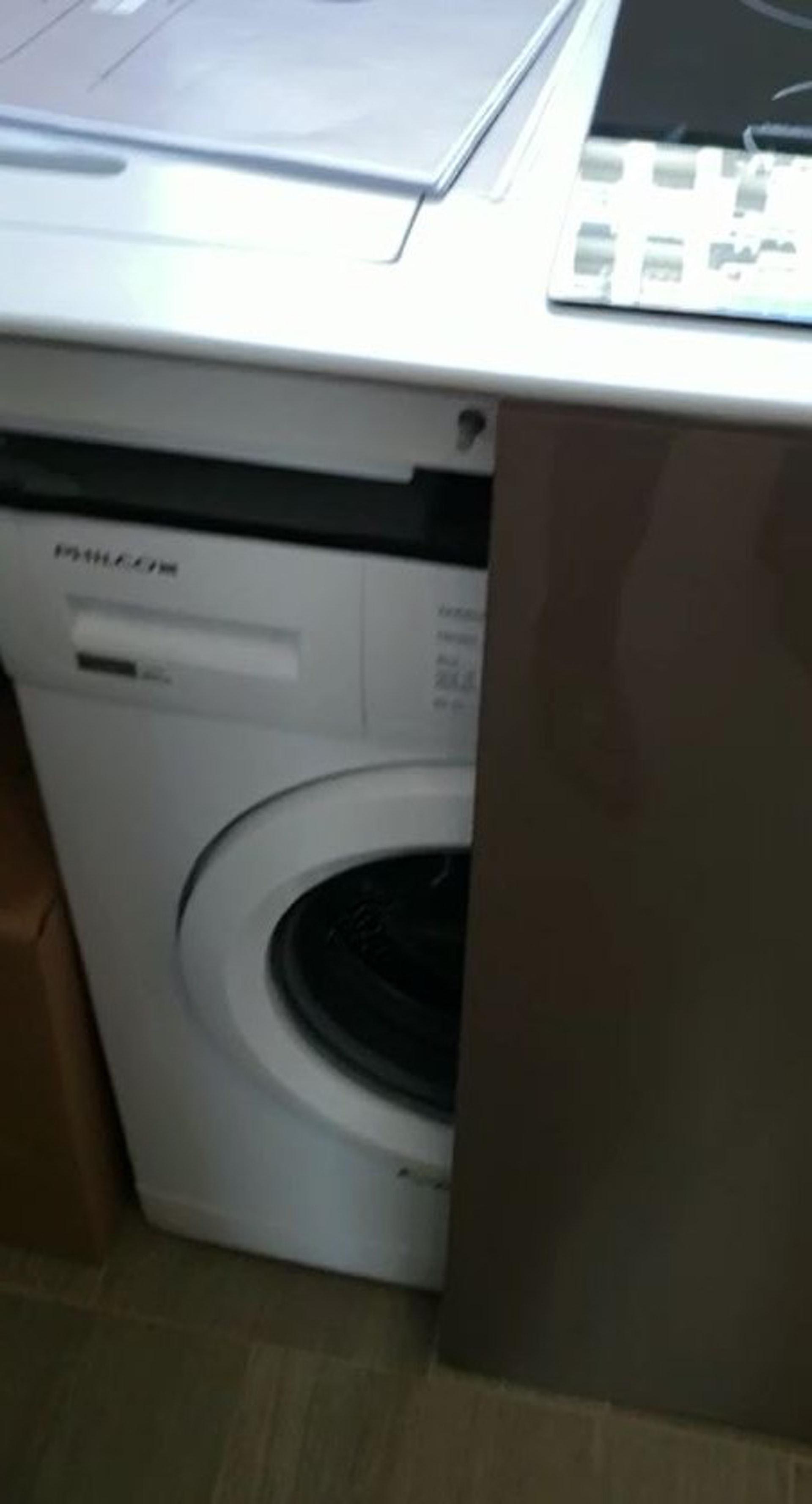 洗衣機放設在開放式廚房的工作枱下。(代理提供片段)