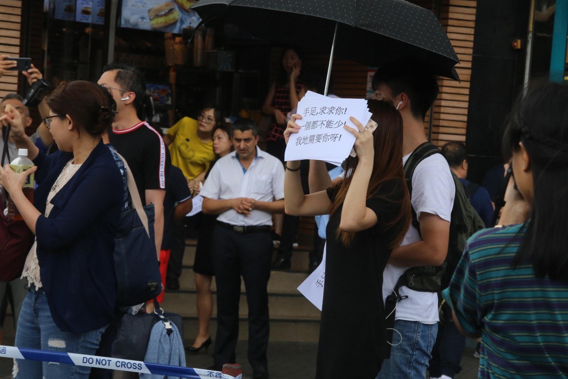 於附近上班的打工仔製作紙牌,希望事主可看到她們的訊息。(陳蕾蕾攝)