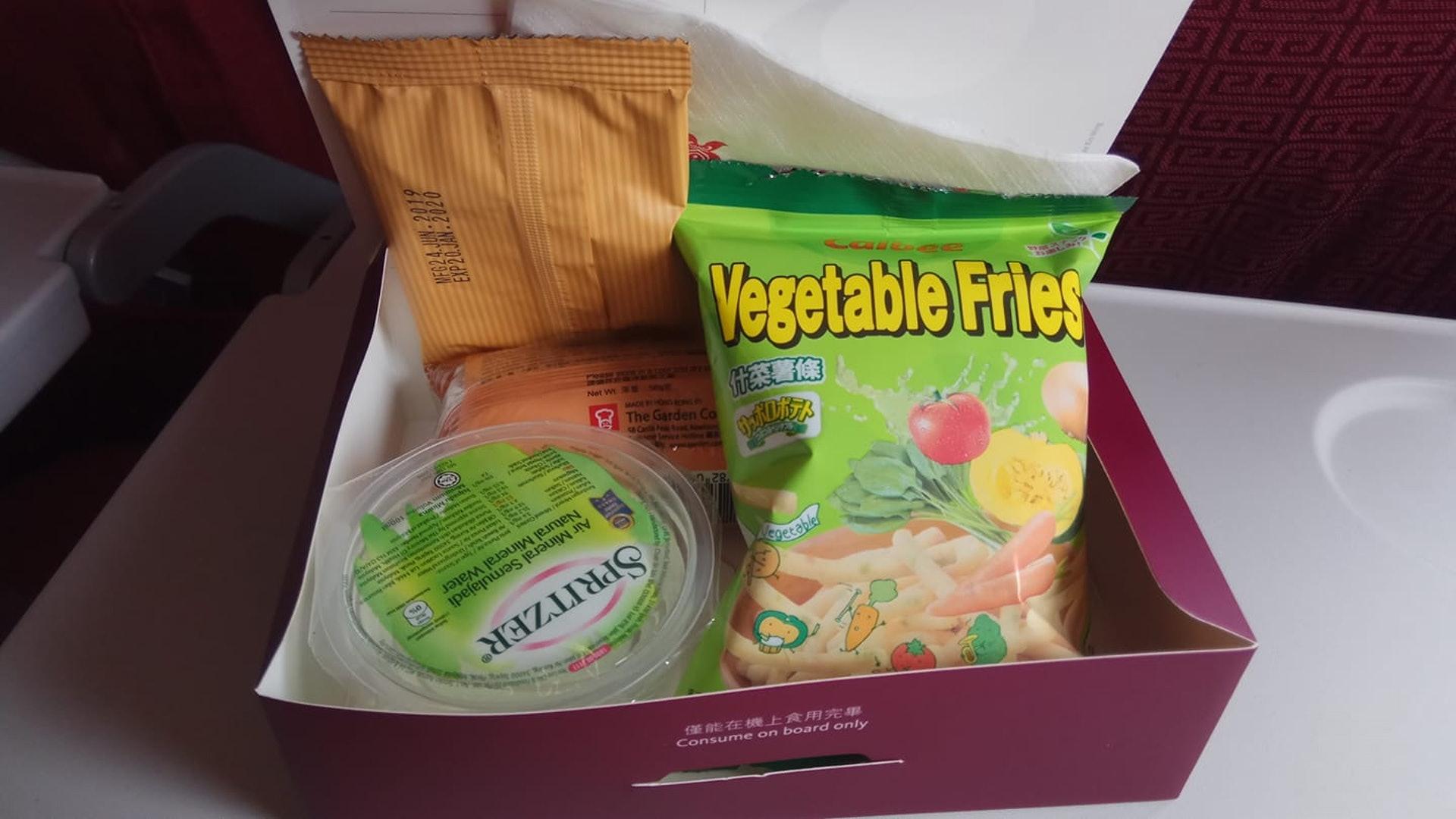 樓主本以為機上提供的餐點是常見的熱食飯餐,但今次竟然送上零食盒,內有餅乾、瑞士卷、薯條及一杯水,令他感到無奈。(fb群組「中伏飲食報料區」圖片)