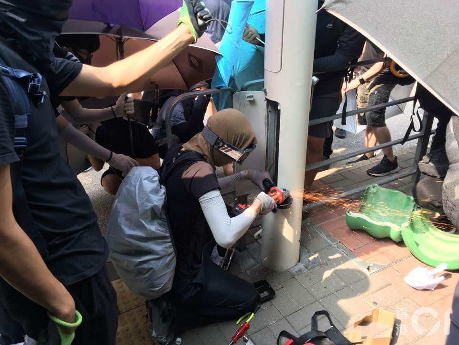 示威者拆起智能燈柱底部的電箱後,再以手電鋸鋸開柱身。(陳浩然攝)