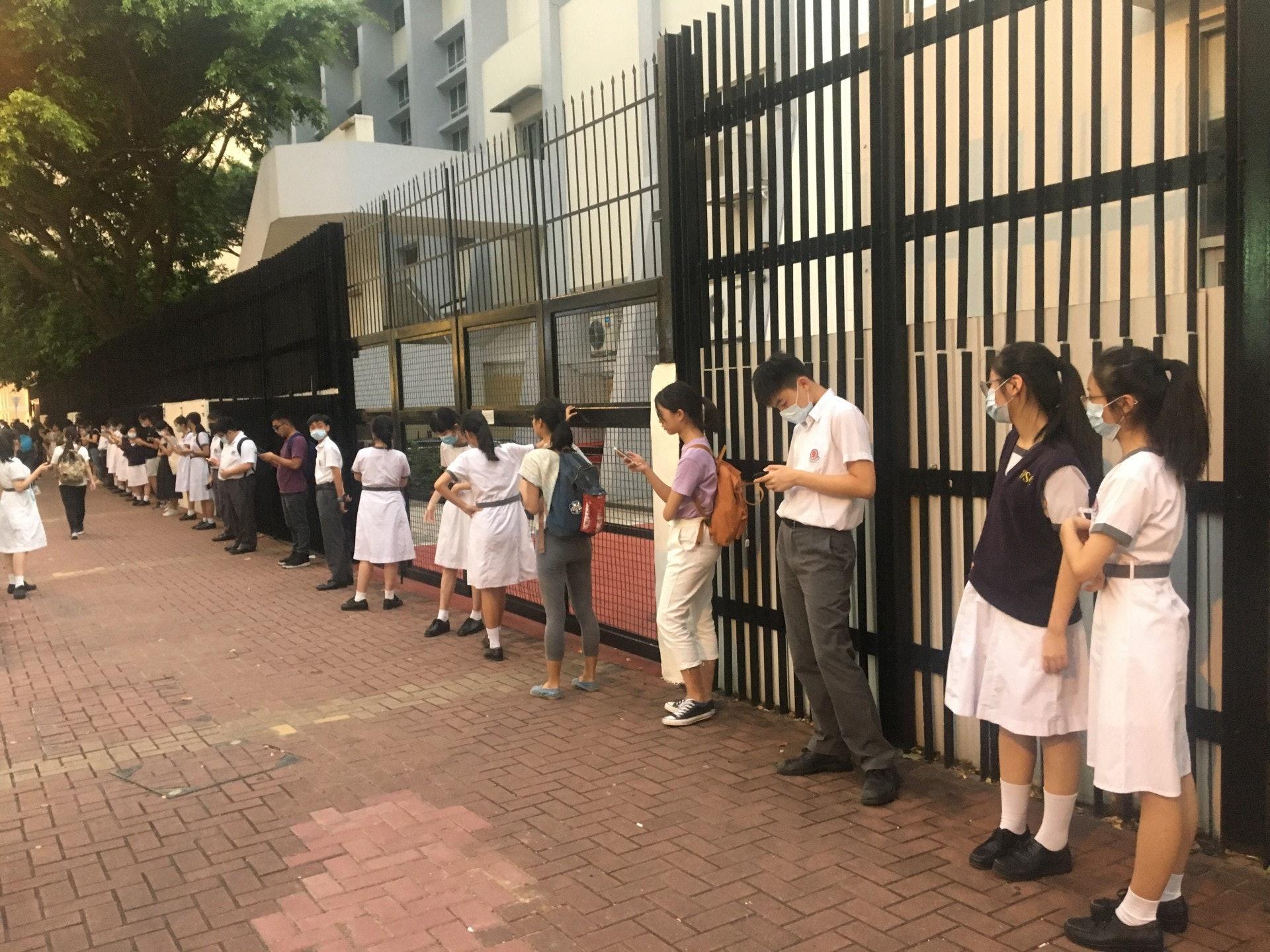 王少清中學校門外有大約30位學生及校友一字排開。(李恩慈攝)