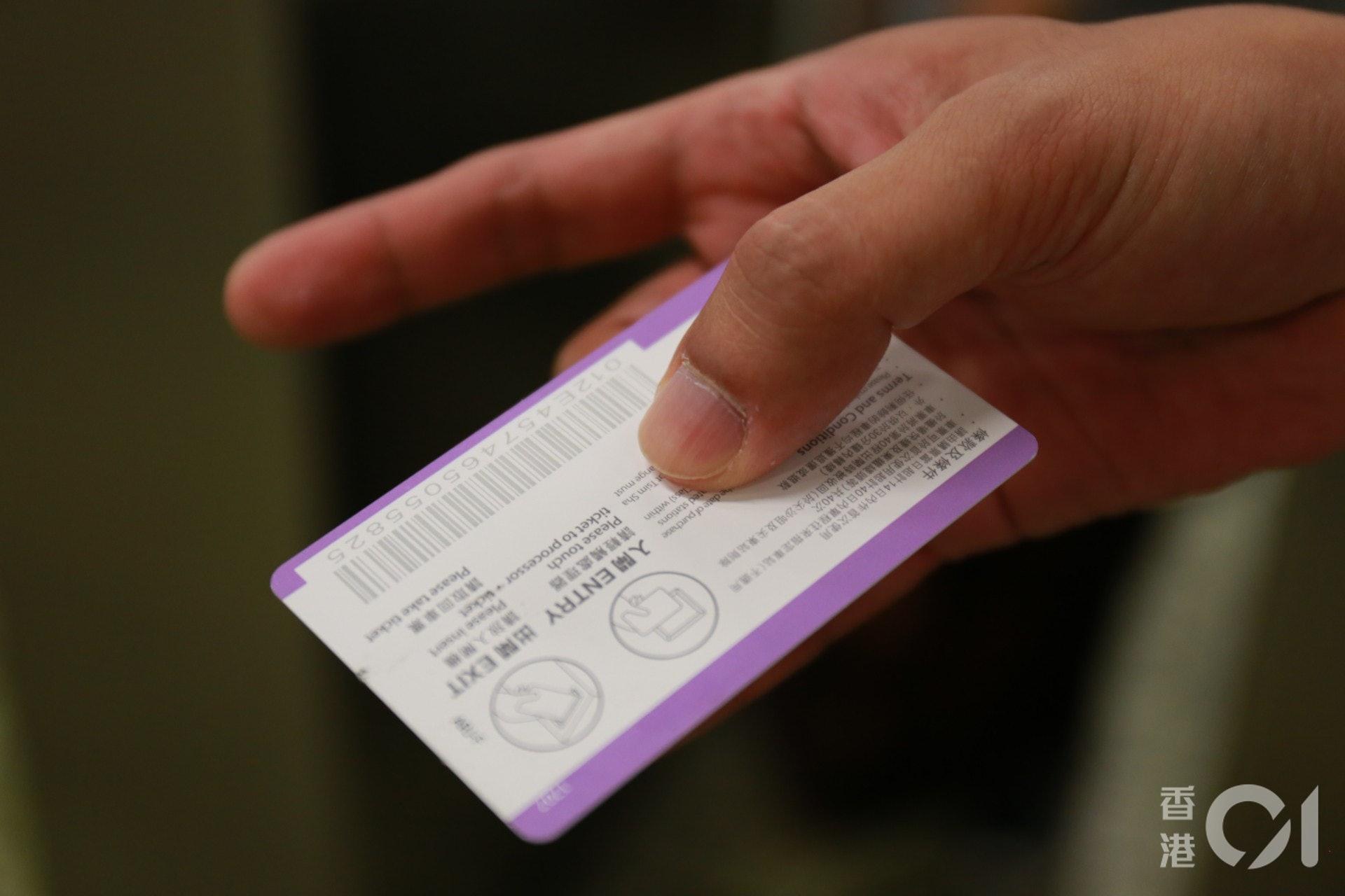 乘客劉先生取出車票時被膠水黏手。(陳諾希攝)