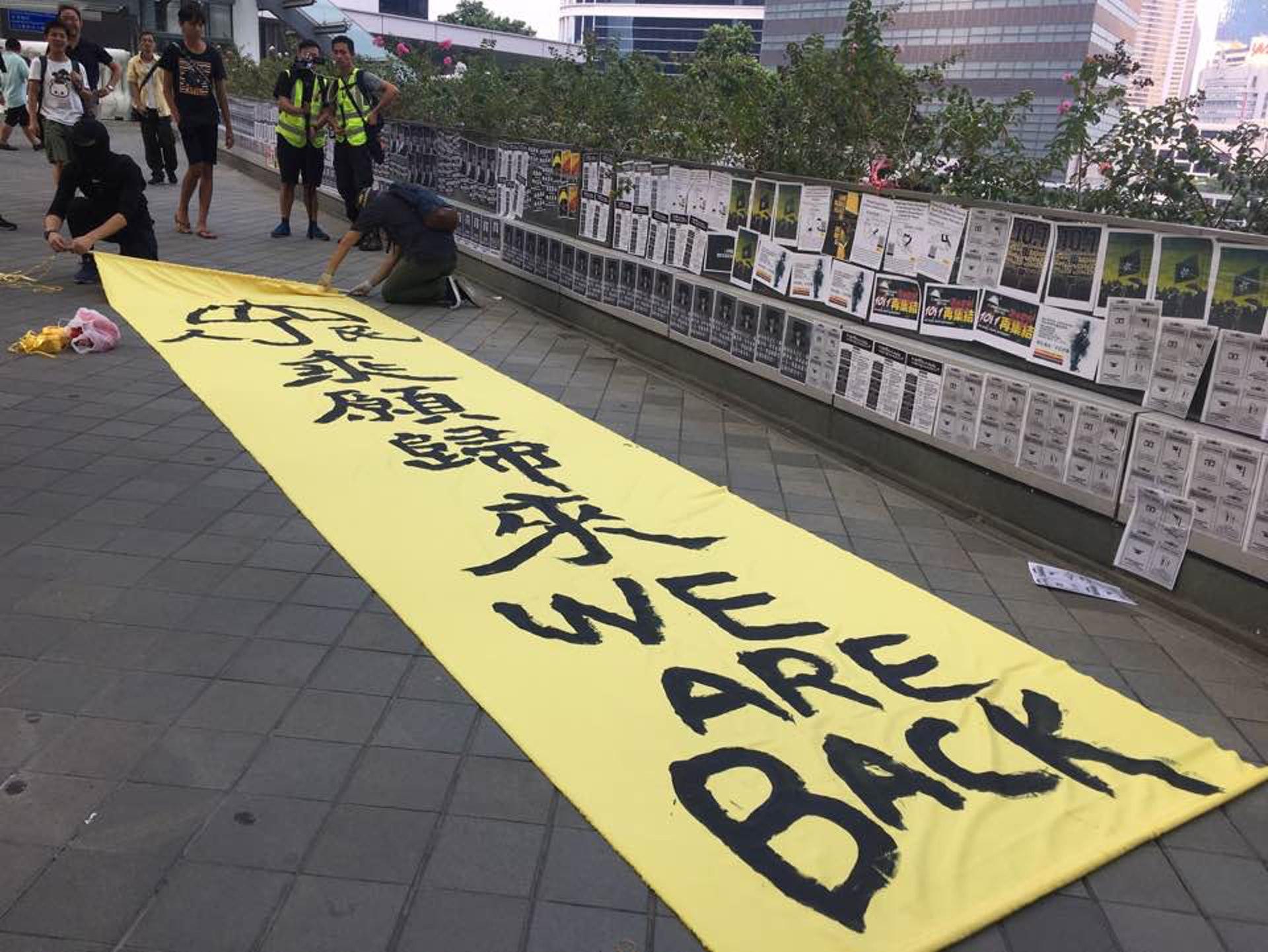 現場亦見到一張寫有「we are back」的大型直幡。(李偉欣攝)