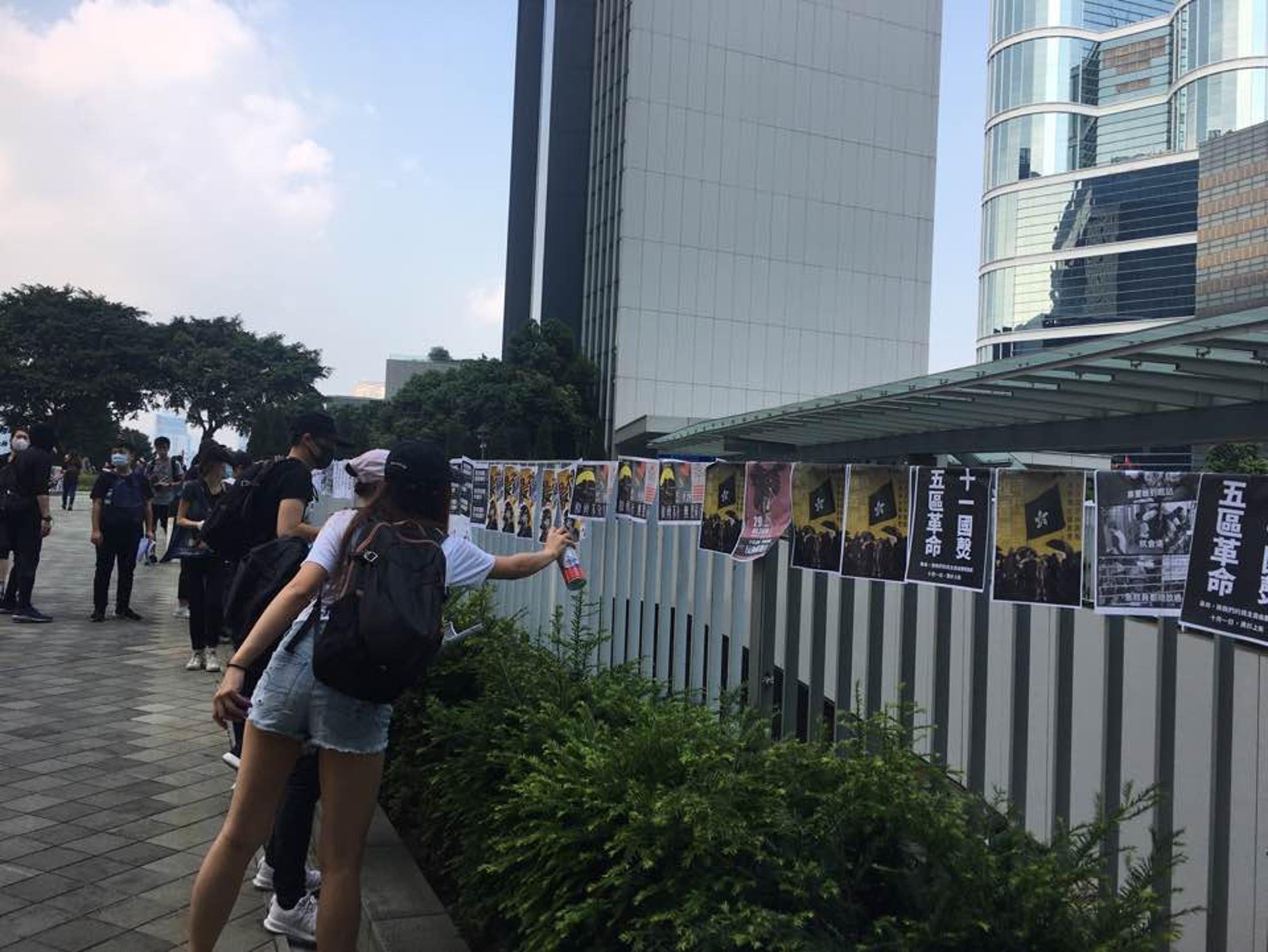 下午3時許,已有年輕人在金鐘一帶貼上宣傳海報。(李偉欣攝)