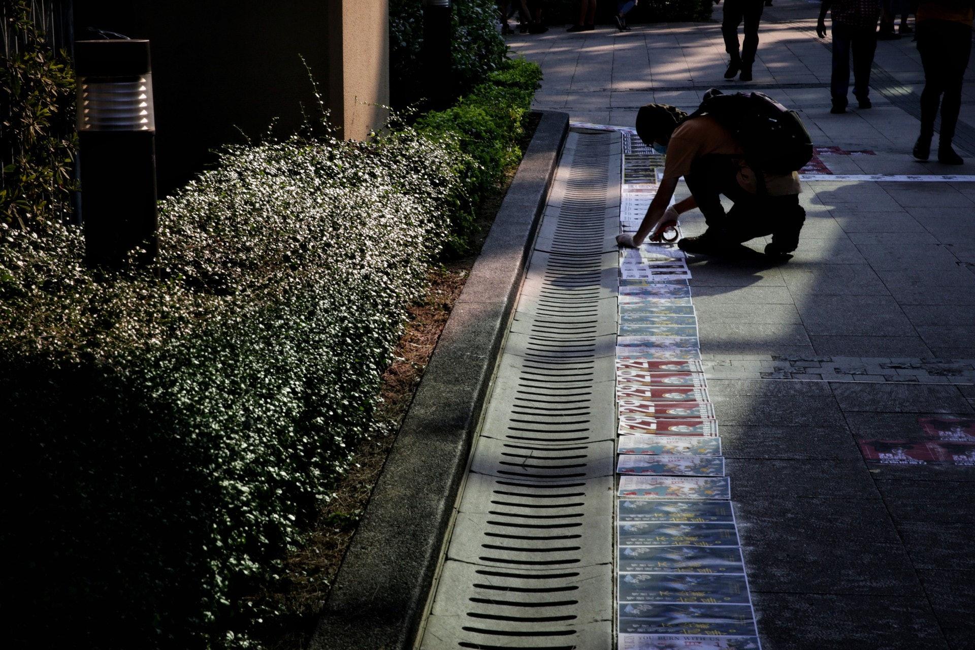 約下午3至4時,已有年青人在金鐘聚集,在地上貼上宣傳海報,形成一條連儂路。(梁鵬威攝)