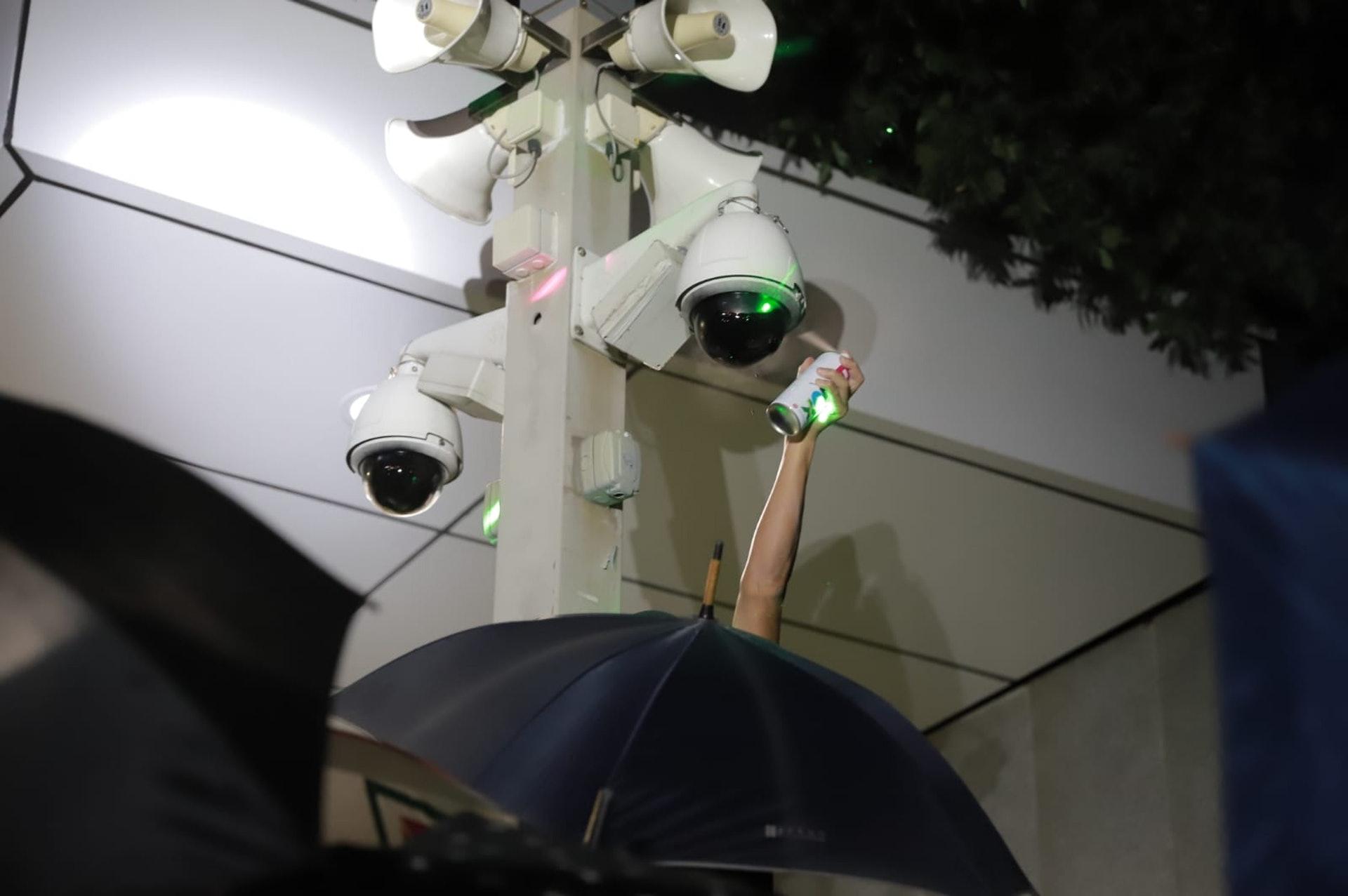 亦有穿黑衣人士噴金鐘一帶的閉路電視。(羅國輝攝)
