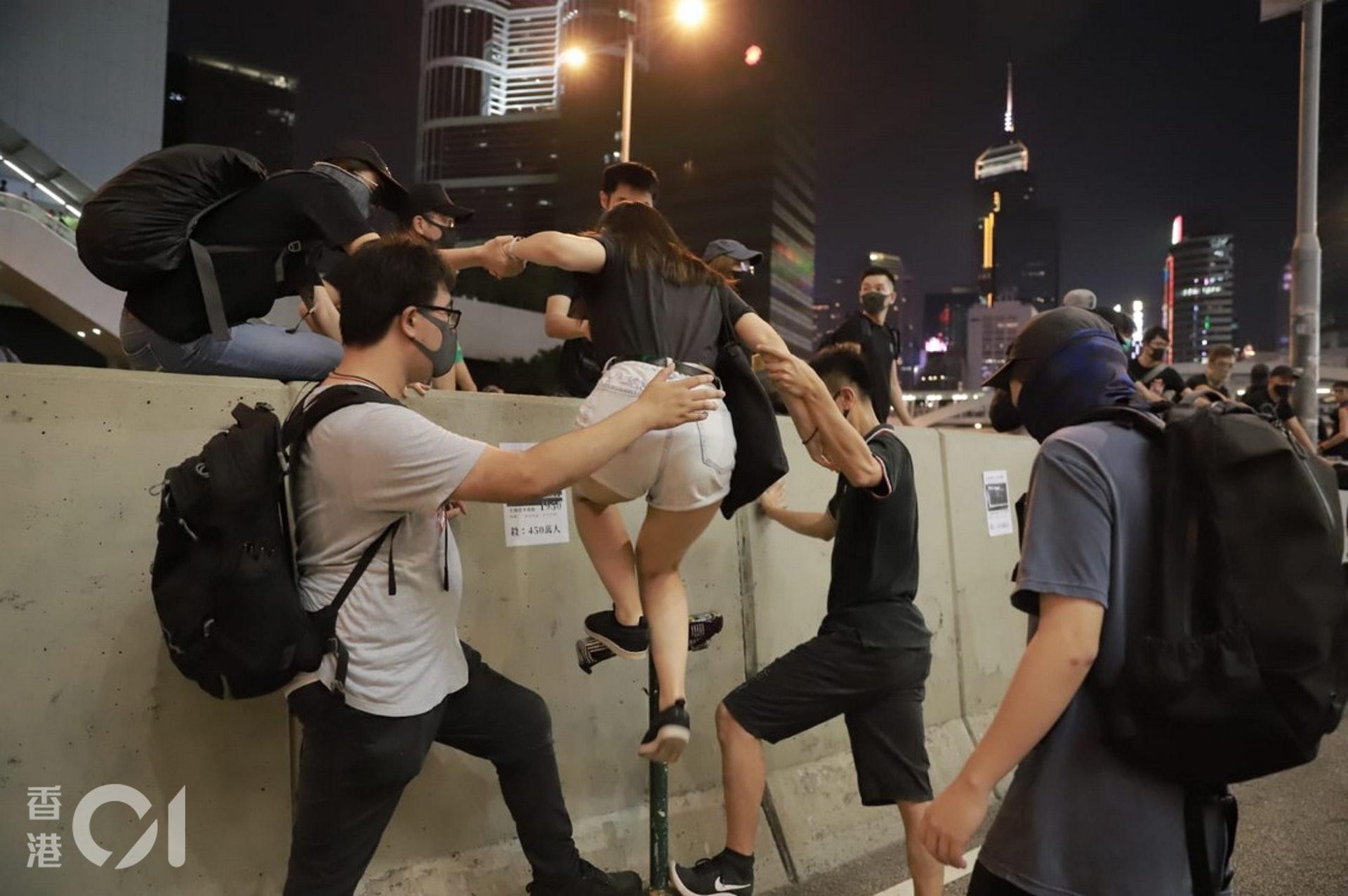 2019年9月28日,示威者互相協助大家跨過夏愨道的石壆。(羅國輝攝)