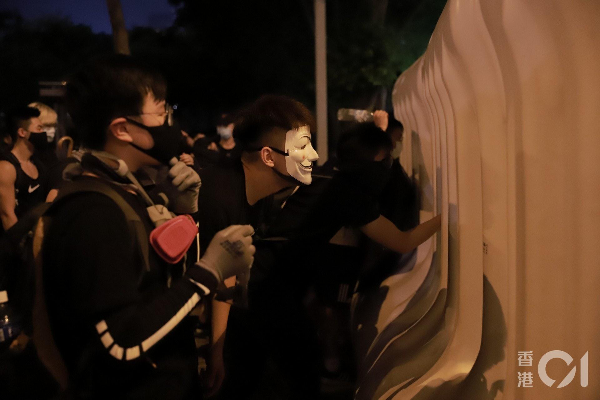 2019年9月28日,有戴上V煞面具的示威者從特首辨外的水馬觀察警方的佈防。(羅國輝攝)