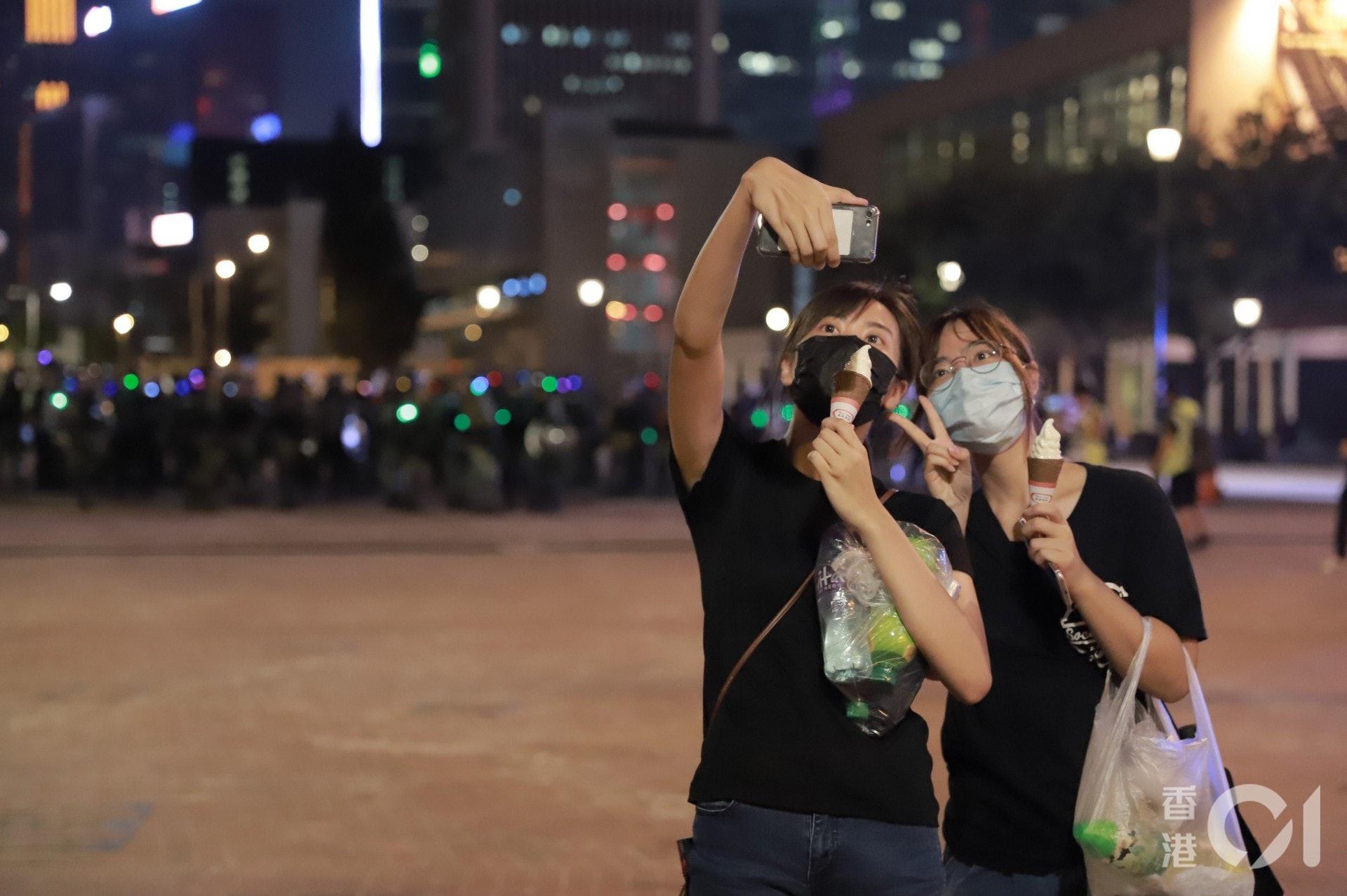 2019年9月28日,有購買雪糕後的市民在防暴警察防線前自拍。(羅國輝攝)