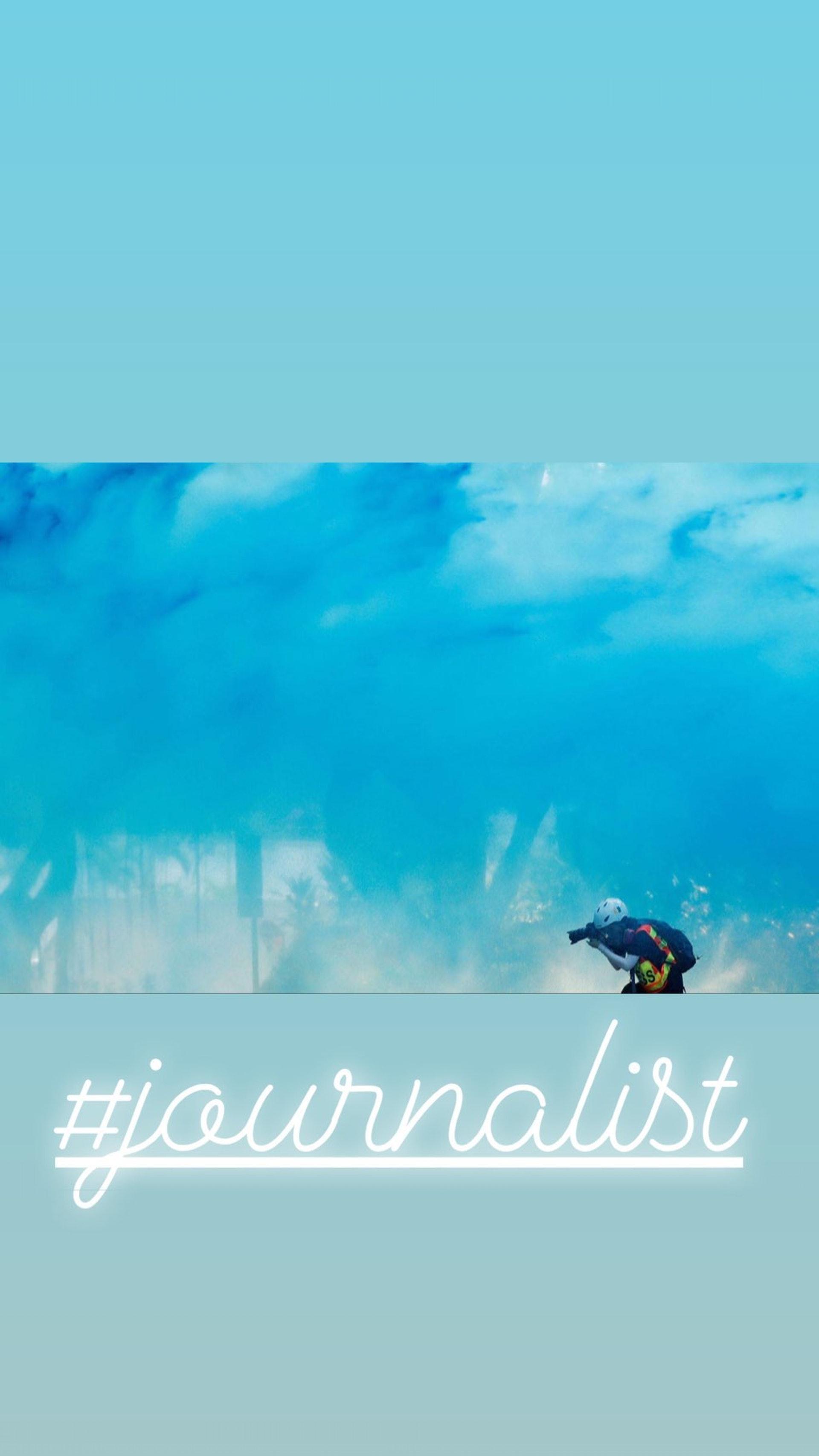 梁凱寧分享一名前線記者在彌漫着一片藍色的空氣中舉起相機報道的照片。(Instagram:@maggieleung0722)