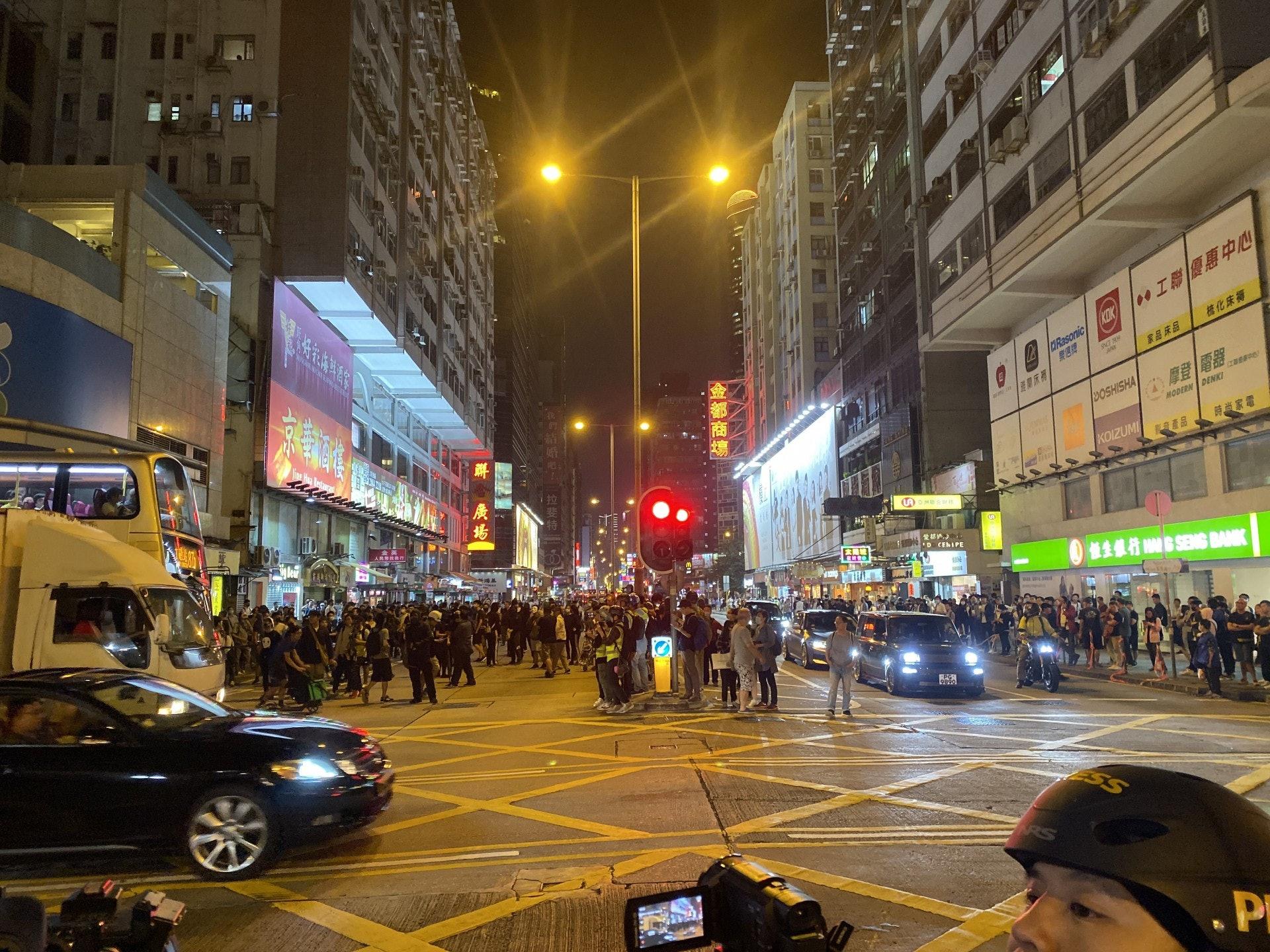 多名黑衣示威者步出彌敦道。(陳浩然攝)