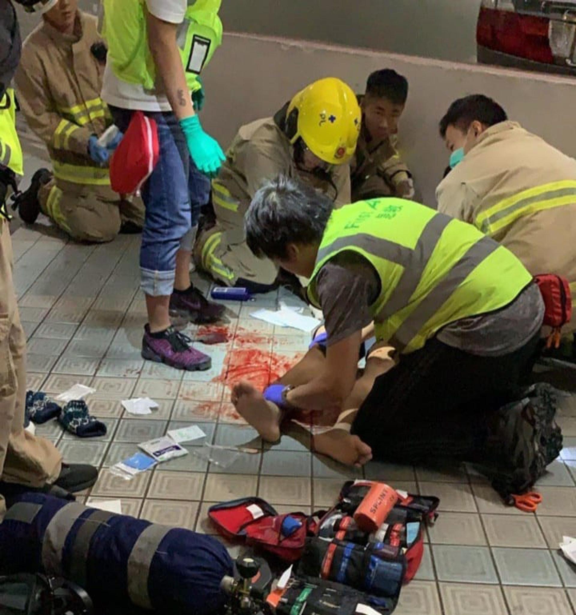 救援人員在場拯救墮樓青年。(網上圖片)