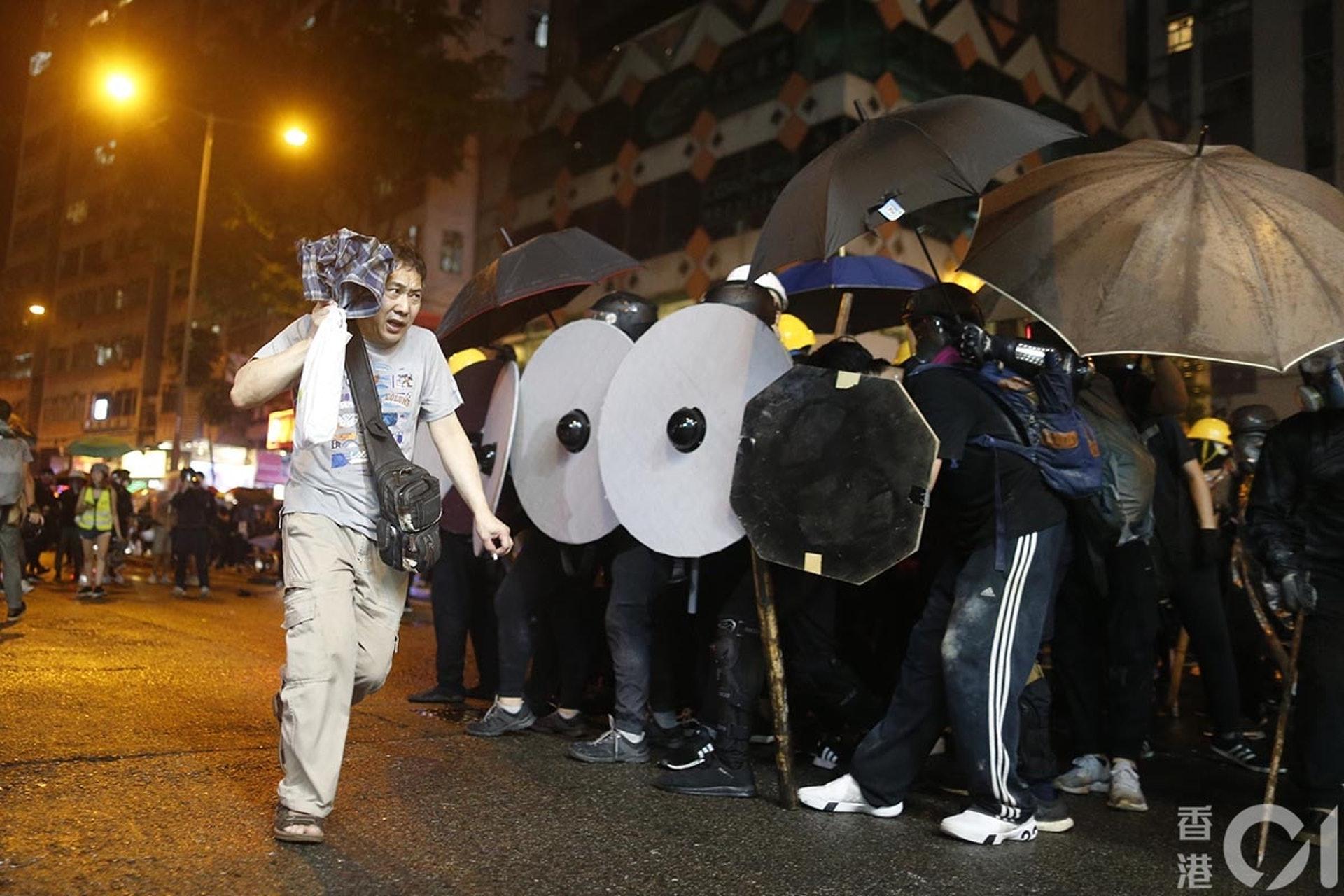 831遊行示威衝突,晚上8點多,警方在灣仔與示威者對峙,路過市民驚慌。(梁鵬威攝)