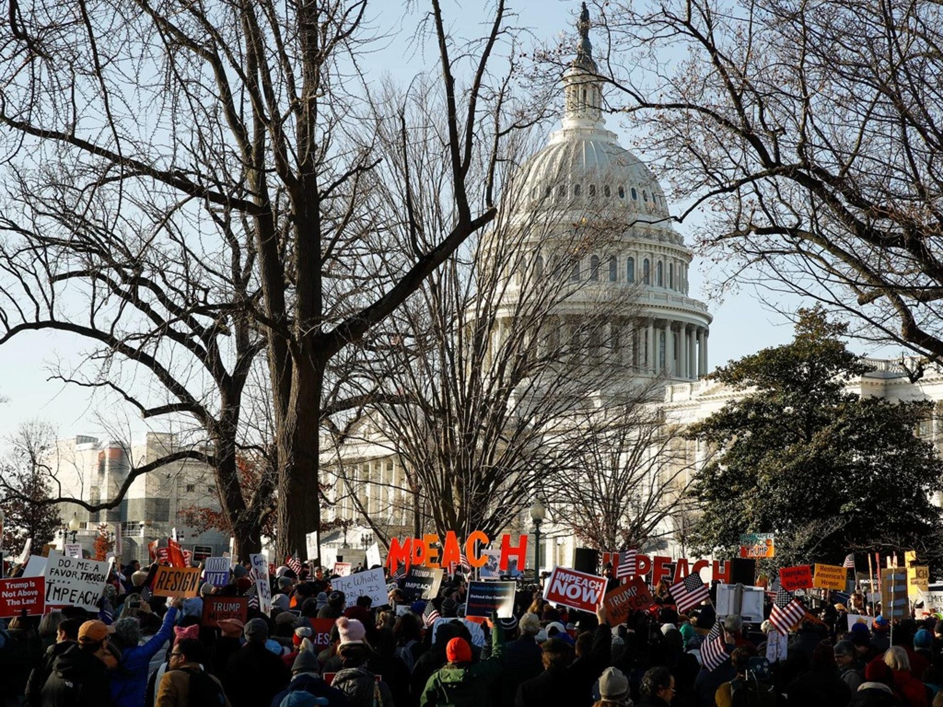 2019年12月18日,美國眾議院通過針對特朗普的彈劾條款之際,支持彈劾的示威人士聚集在國會山外。(AP)