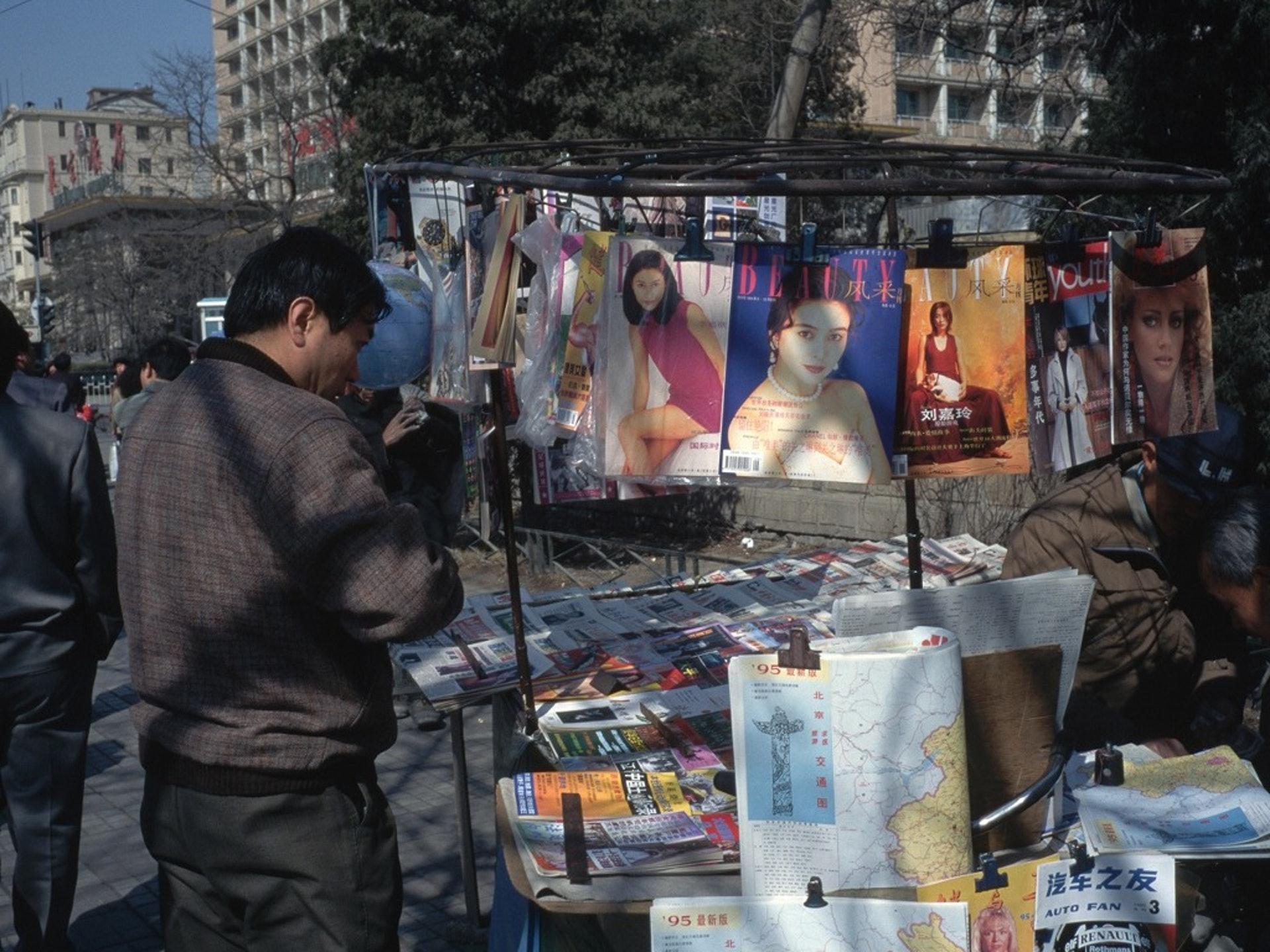 在20世紀90年代中期,中國仍是一個輸出輕工業品的發展中國家,圖為1995年的北京,很多居民獲取信息的唯一渠道甚至除了電視就只有報攤。(Getty)
