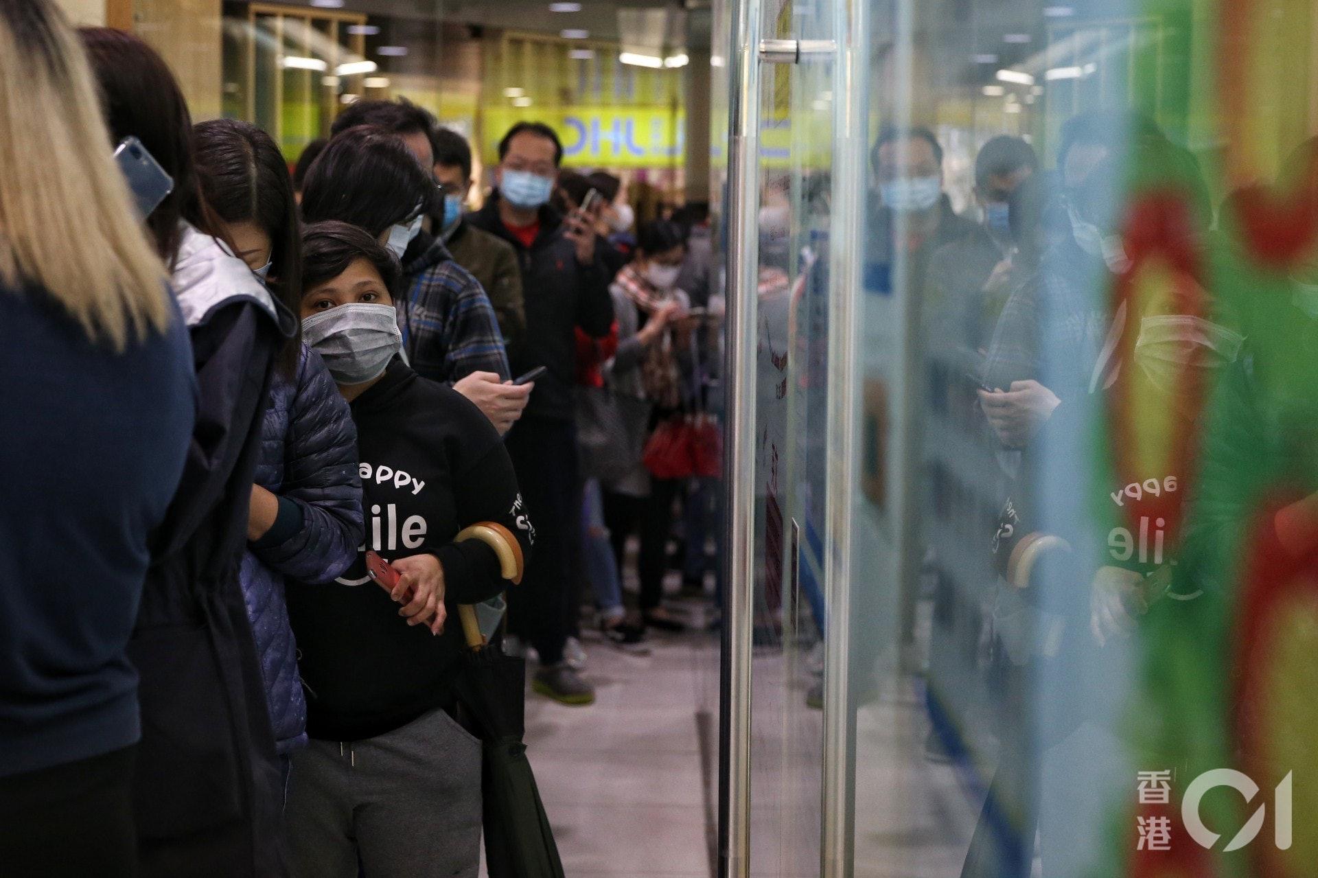 武漢肺炎在港肆虐,不少市民連日到連鎖日用品店排隊買口罩。(梁鵬威攝)