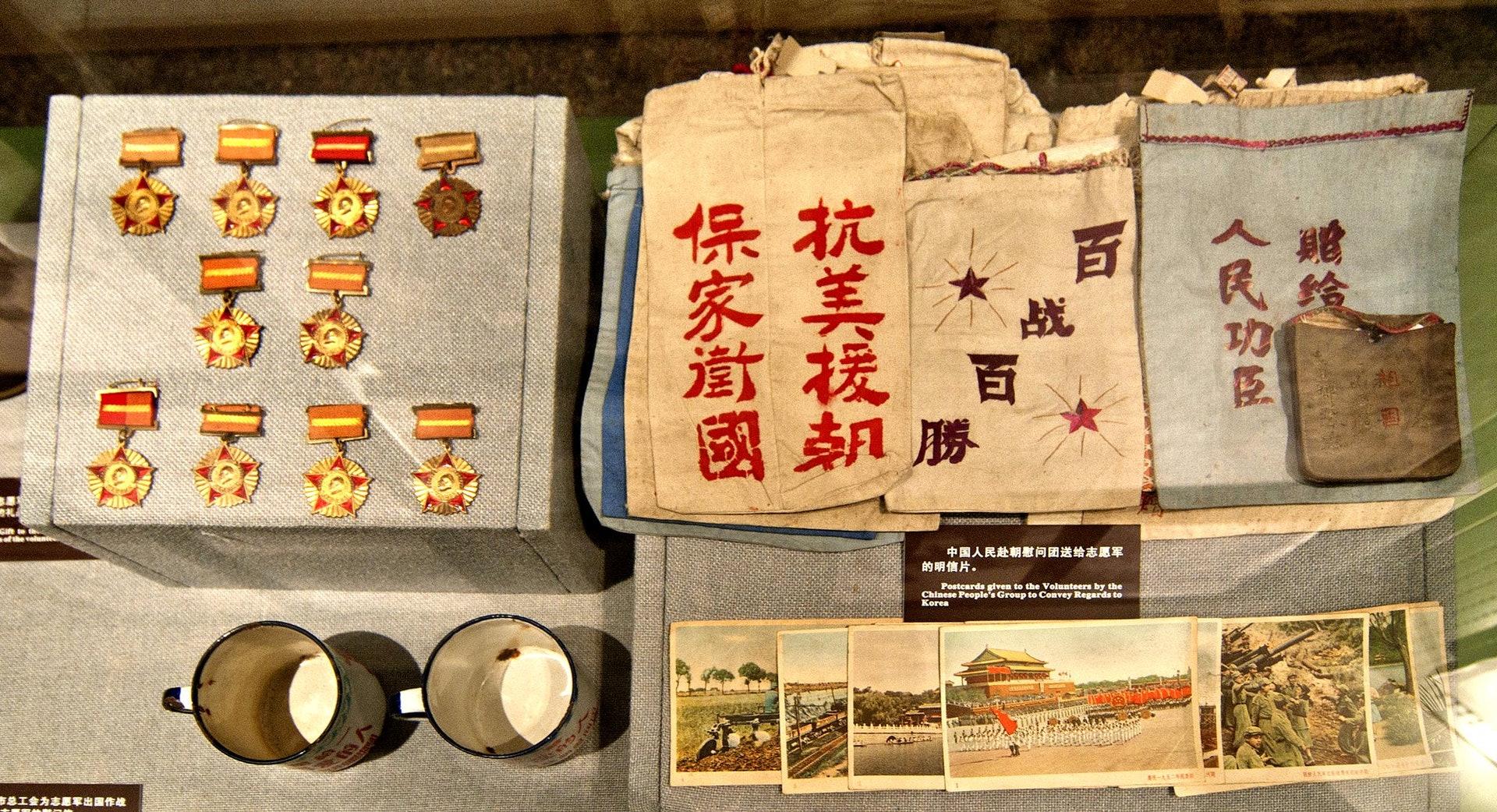 图为辽宁丹东抗美援朝纪念馆里,中国人民赴朝鲜慰问团赠给志愿军的明信片等物品和授给志愿军的奖章。(视觉中国)