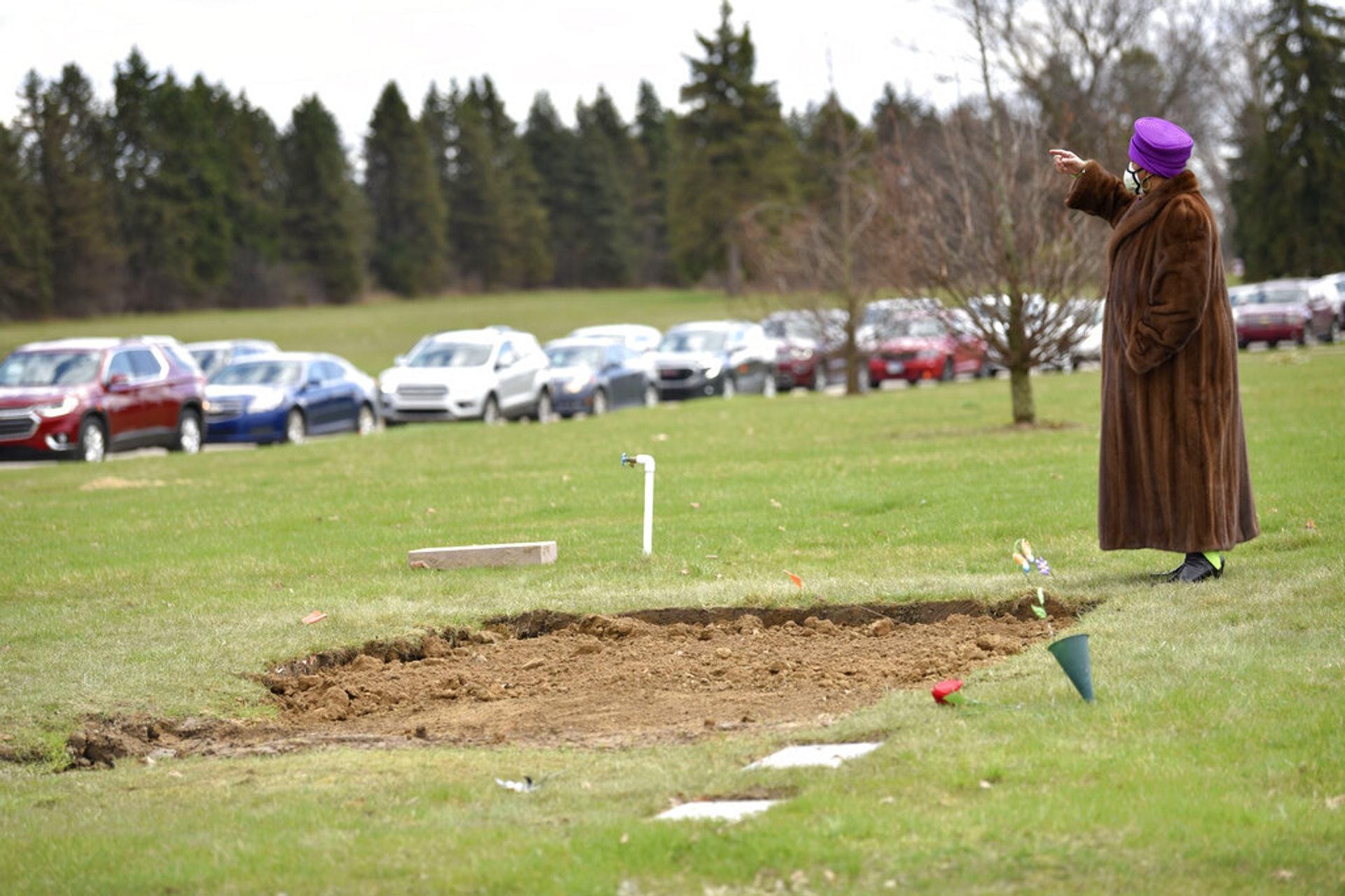 美國新冠肺炎疫情:疫情令許多人痛失家人,其中布朗(Sandy Brown)的丈夫和兒子因感染新冠肺炎死亡。圖為布朗4月10日在密歇根弗林特的墓地向她的親友揮手。(AP)