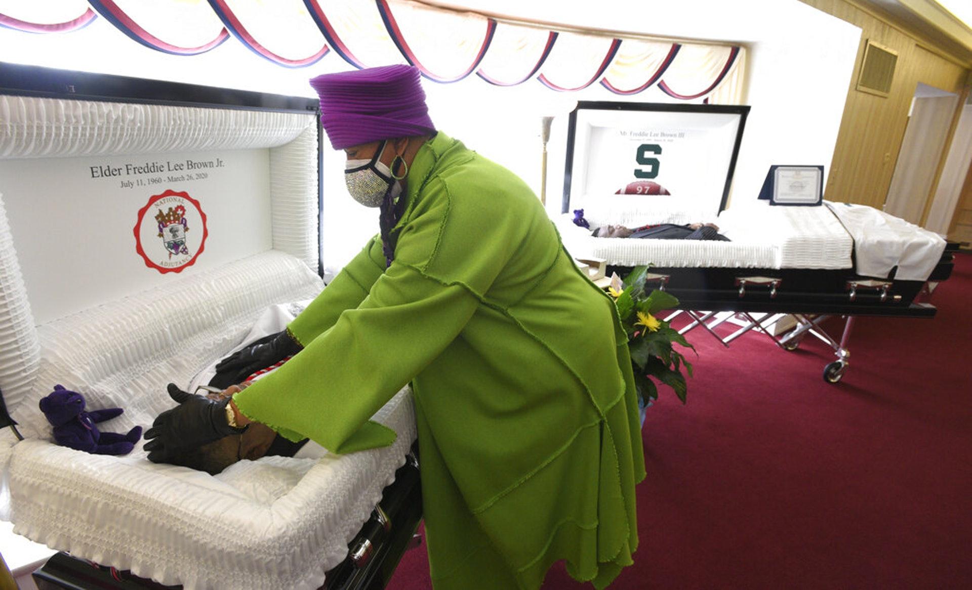 美國新冠肺炎疫情:圖為4月10日,布朗在密歇根弗林特的殯儀館撫摸她丈夫遺體的額頭。(AP)