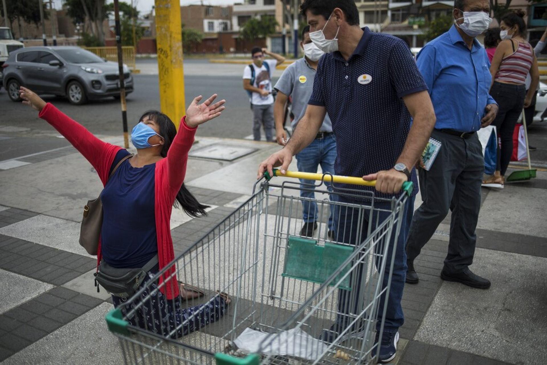 秘魯新冠肺炎疫情:圖為4月11日,一名戴口罩、推着購物車的男子要求路邊一名跪地祈禱的女子讓路。因為她妨礙他進入超市。(AP)