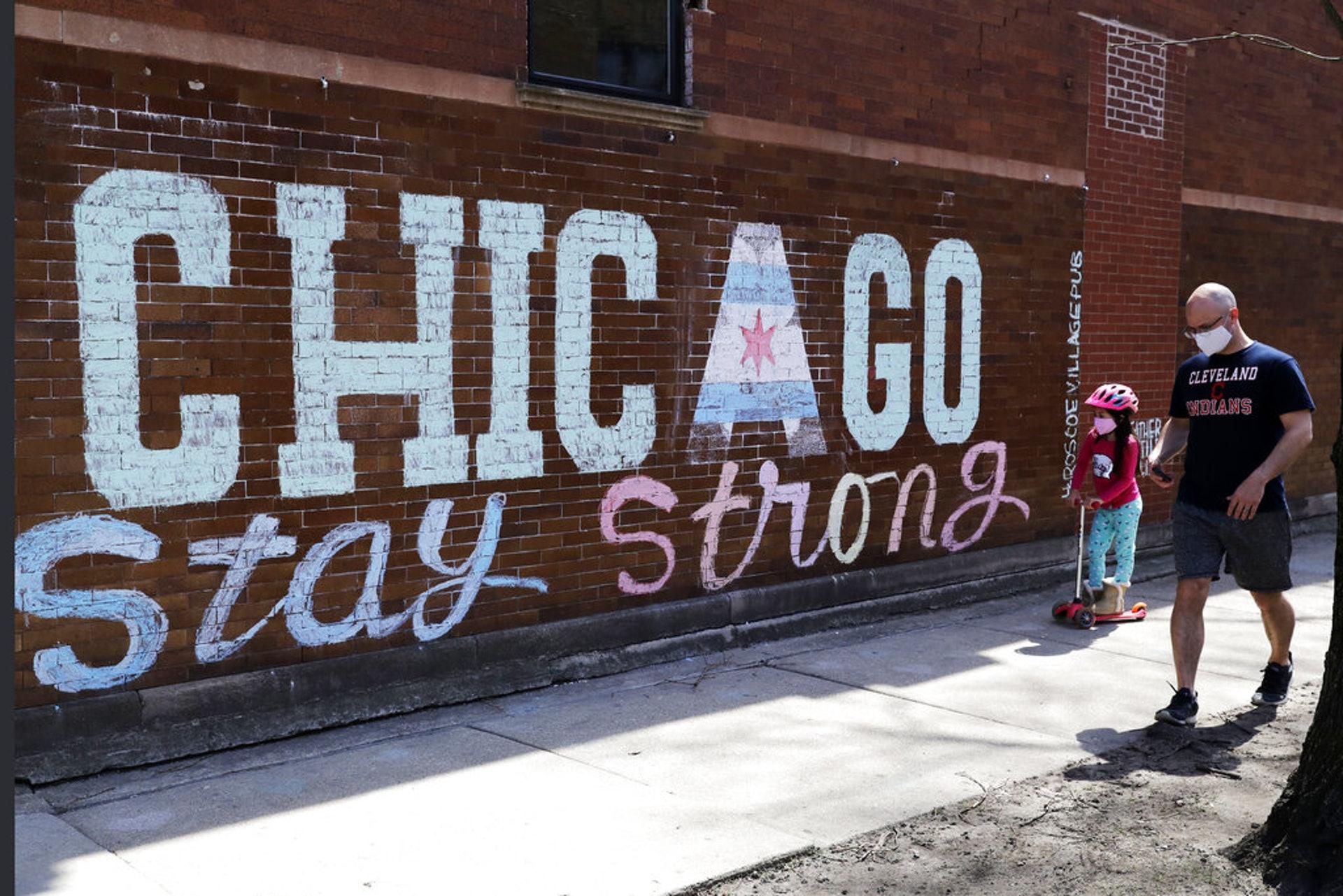 美國新冠肺炎疫情:羅斯科村附近一間酒吧外一幅牆上寫有「芝加哥保持堅強」。圖為4月11人,一名戴口罩的男子和一名戴口罩的孩子經過這幅牆。(AP)