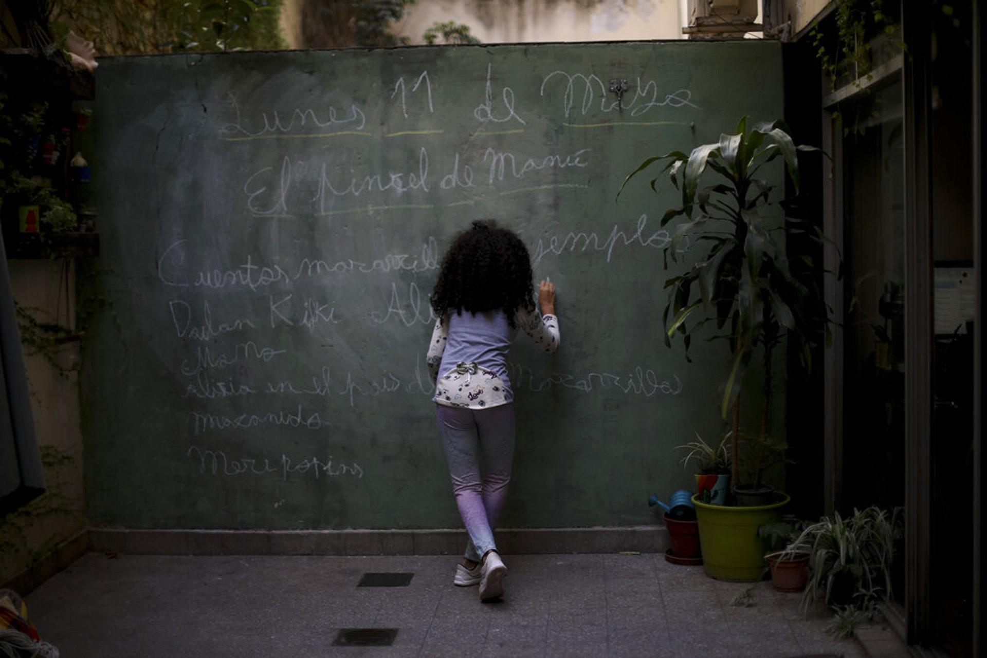 阿根廷新冠肺炎疫情:圖為5月11日布宜諾斯艾利斯一名女子利用家中一面牆當成黑板書寫。