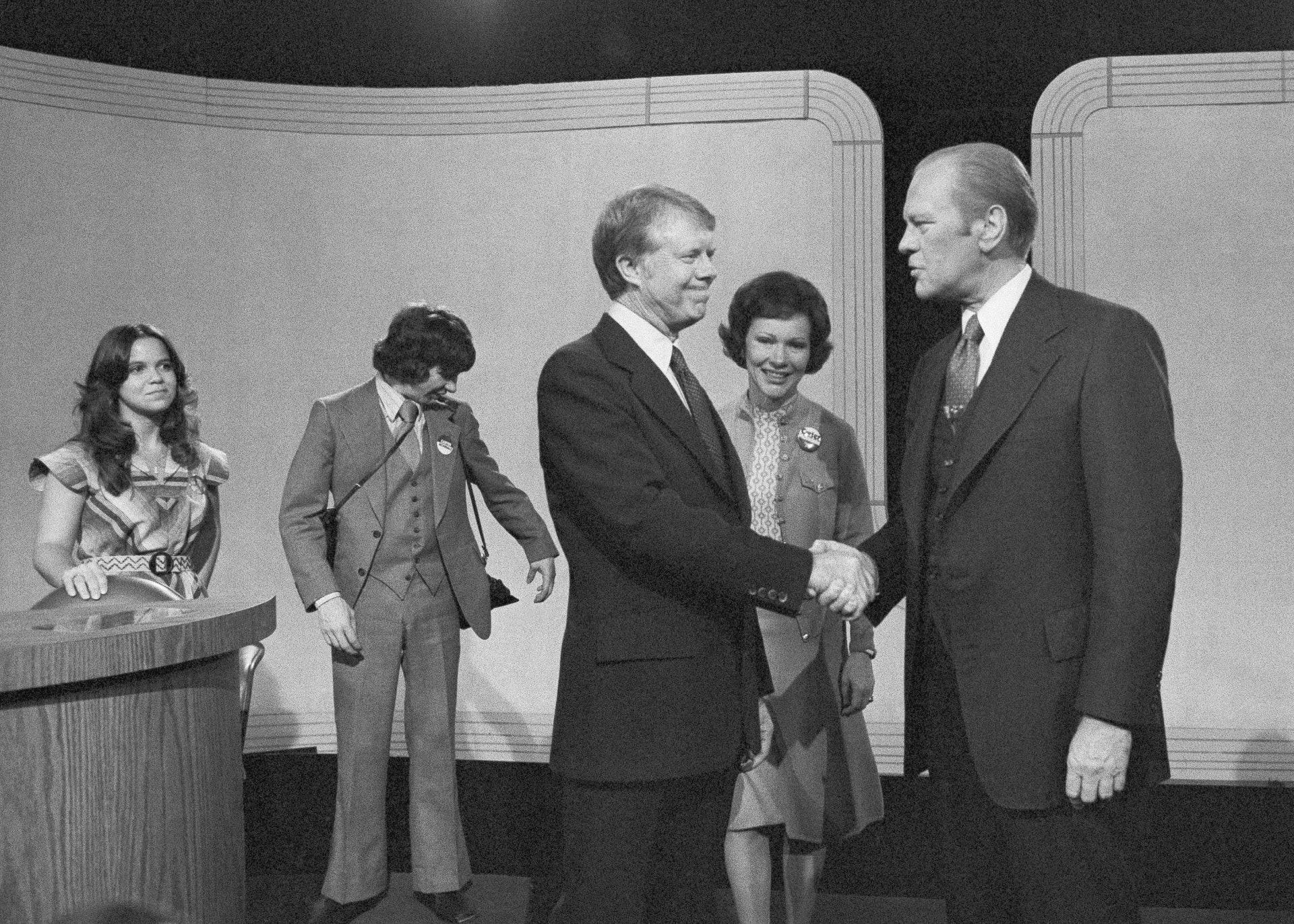美国总统候选人辩论4:美国乔治亚州前州长卡特1976年挑战时任总统福特,二人同年进行时隔16年的首场总统电视辩论。 卡特最终胜出大选,成为美国总统。 图为1976年10月6日卡特在三藩市与福特进行辩论,二人在总结环节时握手。 (AP)