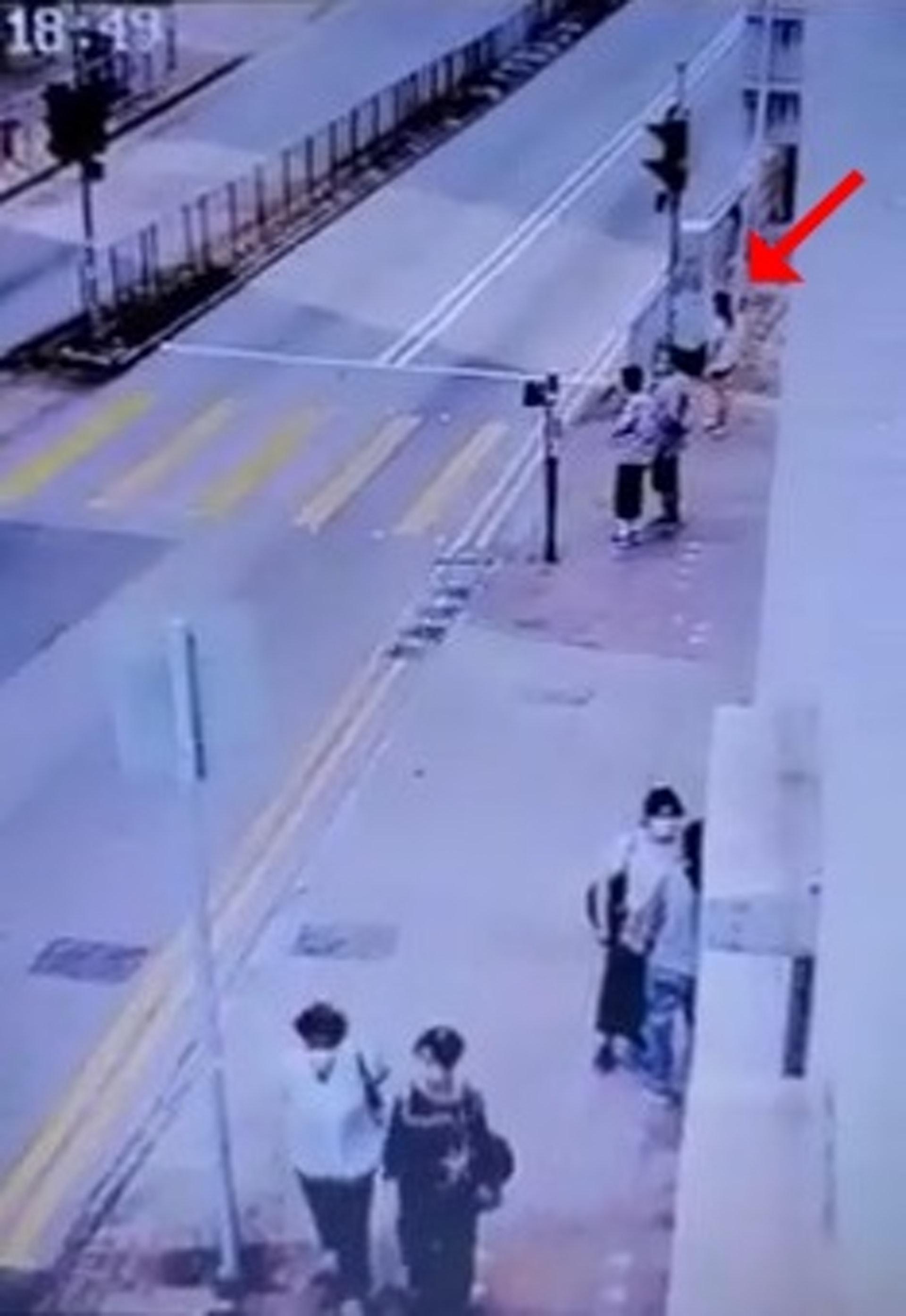 長髮女事主在燈位等候過路,當時尚有兩名途人一同等候。(網上影片截圖)