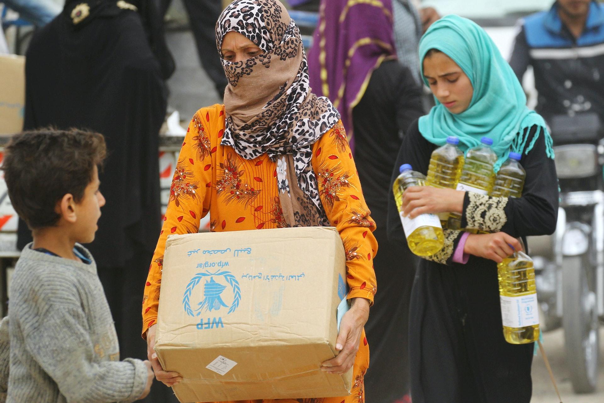 图为2018年4月,在叙利亚拉卡的妇女获取来自世界粮食计划署的援助食物(Reuters)