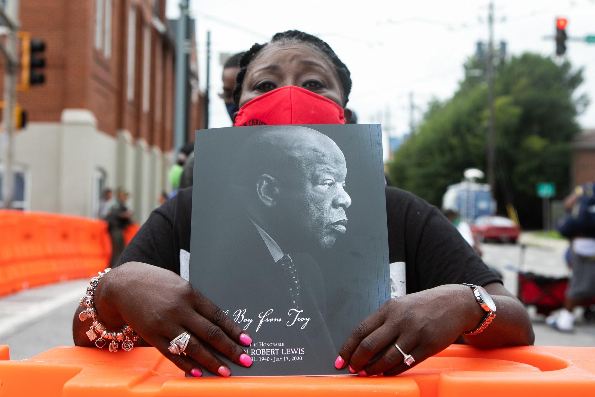 喬治亞州雖然是民主黨籍總統卡特(Jimmy Carter)的出世地以及已故著名黑人民權領袖兼眾議員劉易斯(John Lewis)的根據地,但這個傳統紅州對上一次選出民主黨總統候選人就已經要數到1992年的克林頓(Bill Clinton)。圖為2020年7月30日,劉易斯的葬禮於亞特蘭大舉行,有人手持相片告別。(Getty Images)
