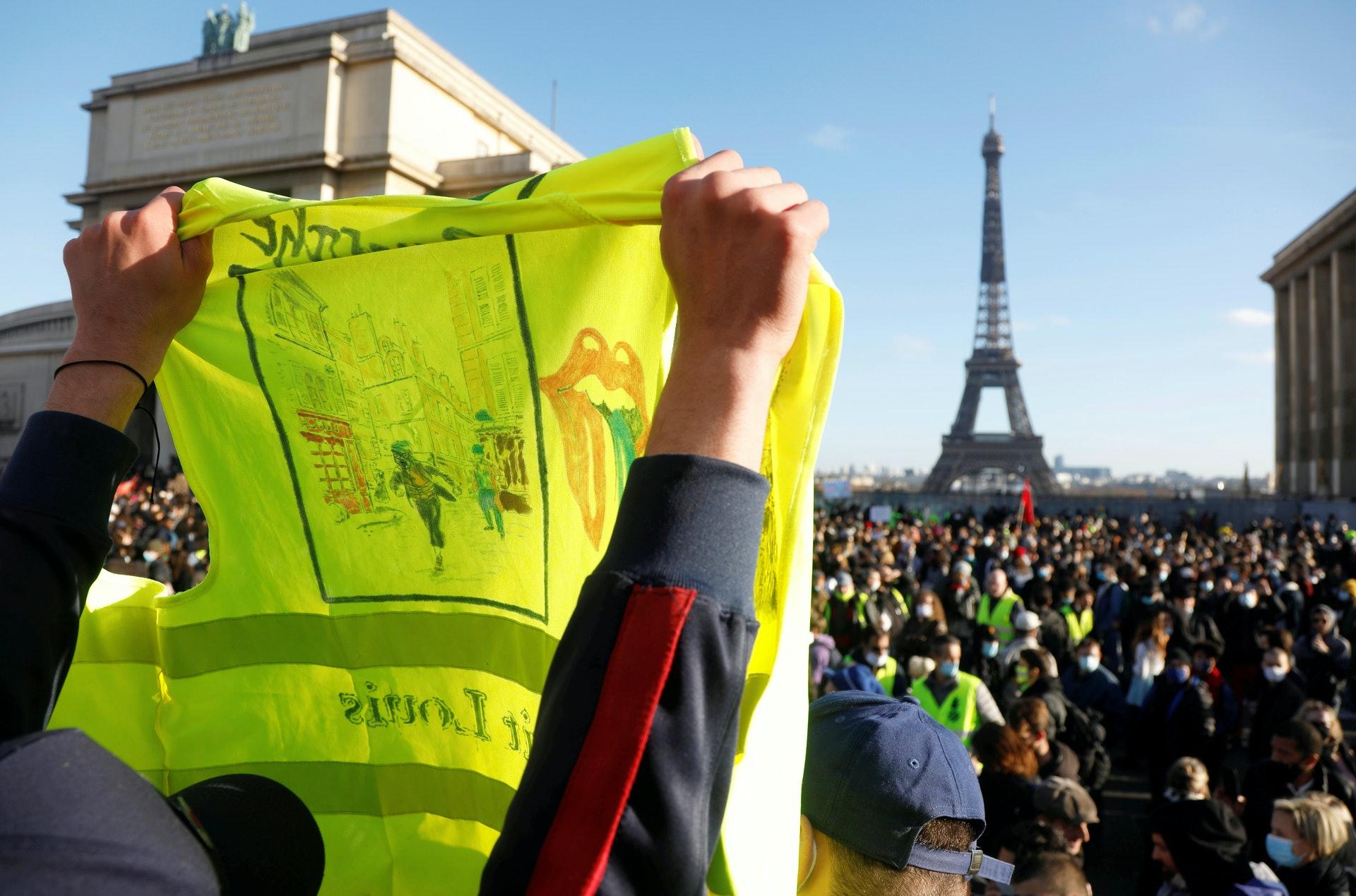 法國示威:巴黎民眾11月21日在特羅卡德羅廣場示威,圖為一名示威者高舉一件黃背心。(Reuters)