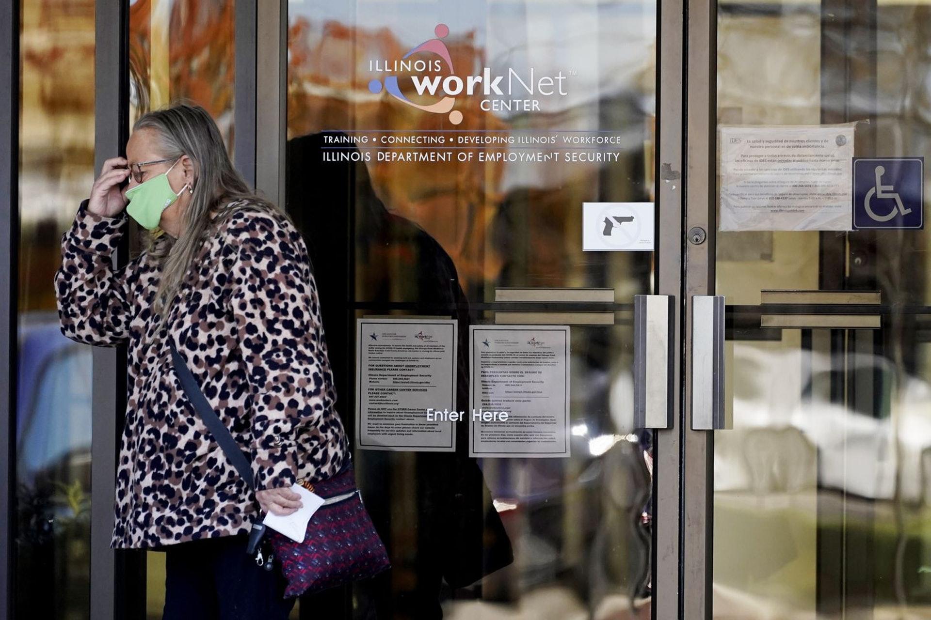 美國領取失業救濟金的人數回升至74.2萬人,圖為伊利諾伊州一位婦女11月從求職中心內走出。(美聯社)