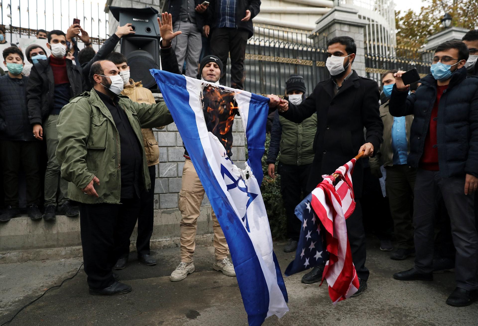 圖為11月28日,伊朗德黑蘭有民眾示威,燒毀美國及以色列國旗,抗議首席核科學家法克里扎德(Mohsen Fakhrizadeh)被殺。(Reuters)